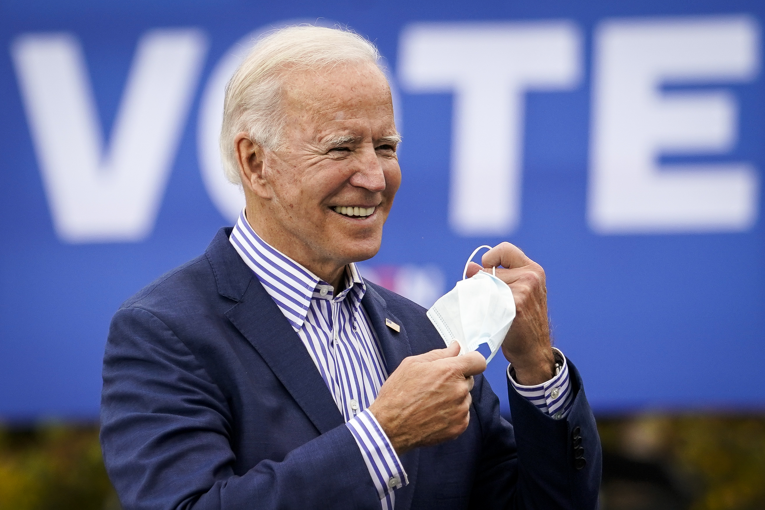 "Biden, in a navy suit jacket, a dress shirt with bold vertical blue and white stripes, and no tie, smiles as he removes a white mask. He stands in the sunlight in front of a massive blue sign that reads, in bold white font, ""VOTE."""