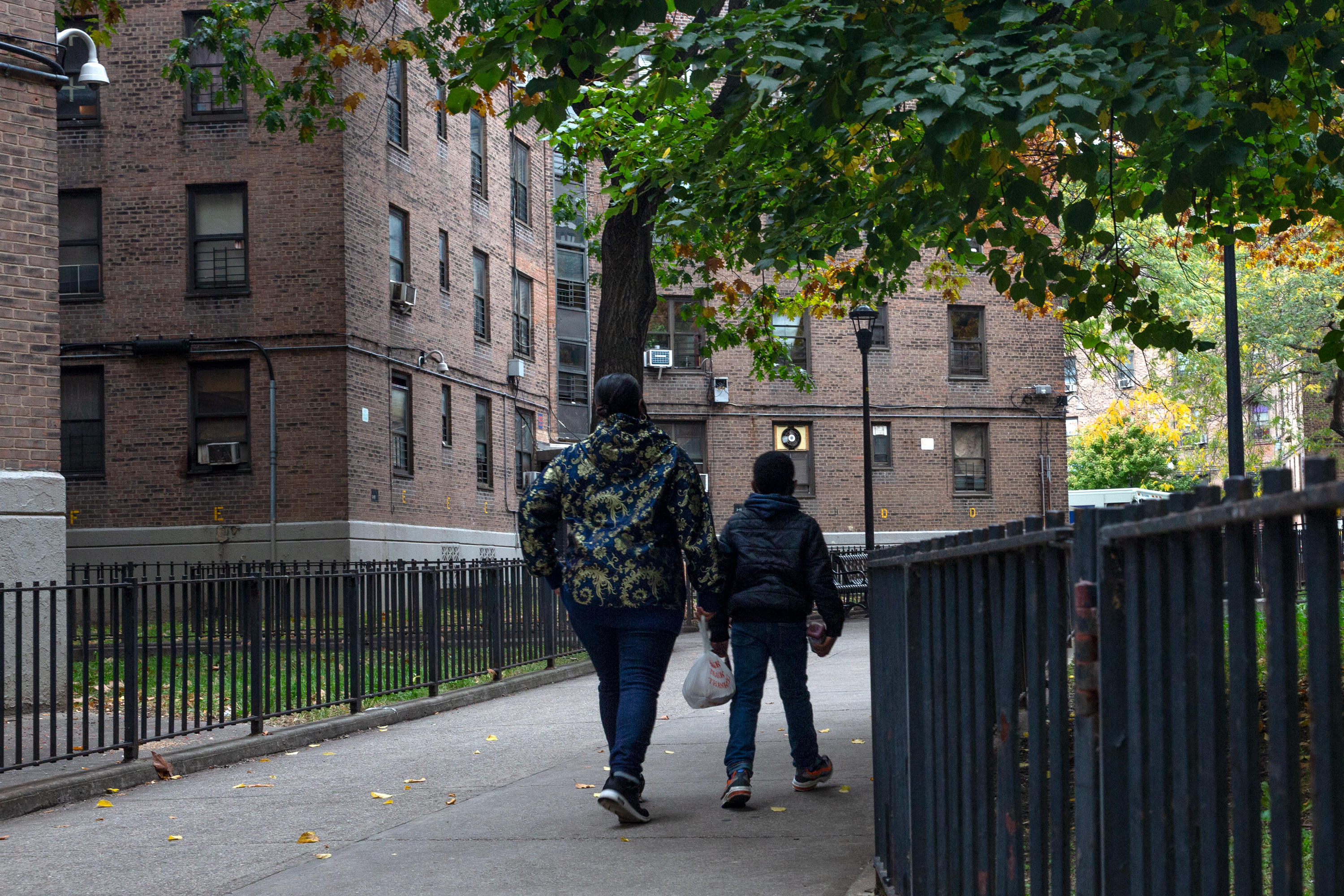A mother walks with her son through the Queensbridge Houses NYCHA complex, Oct. 23, 2020.