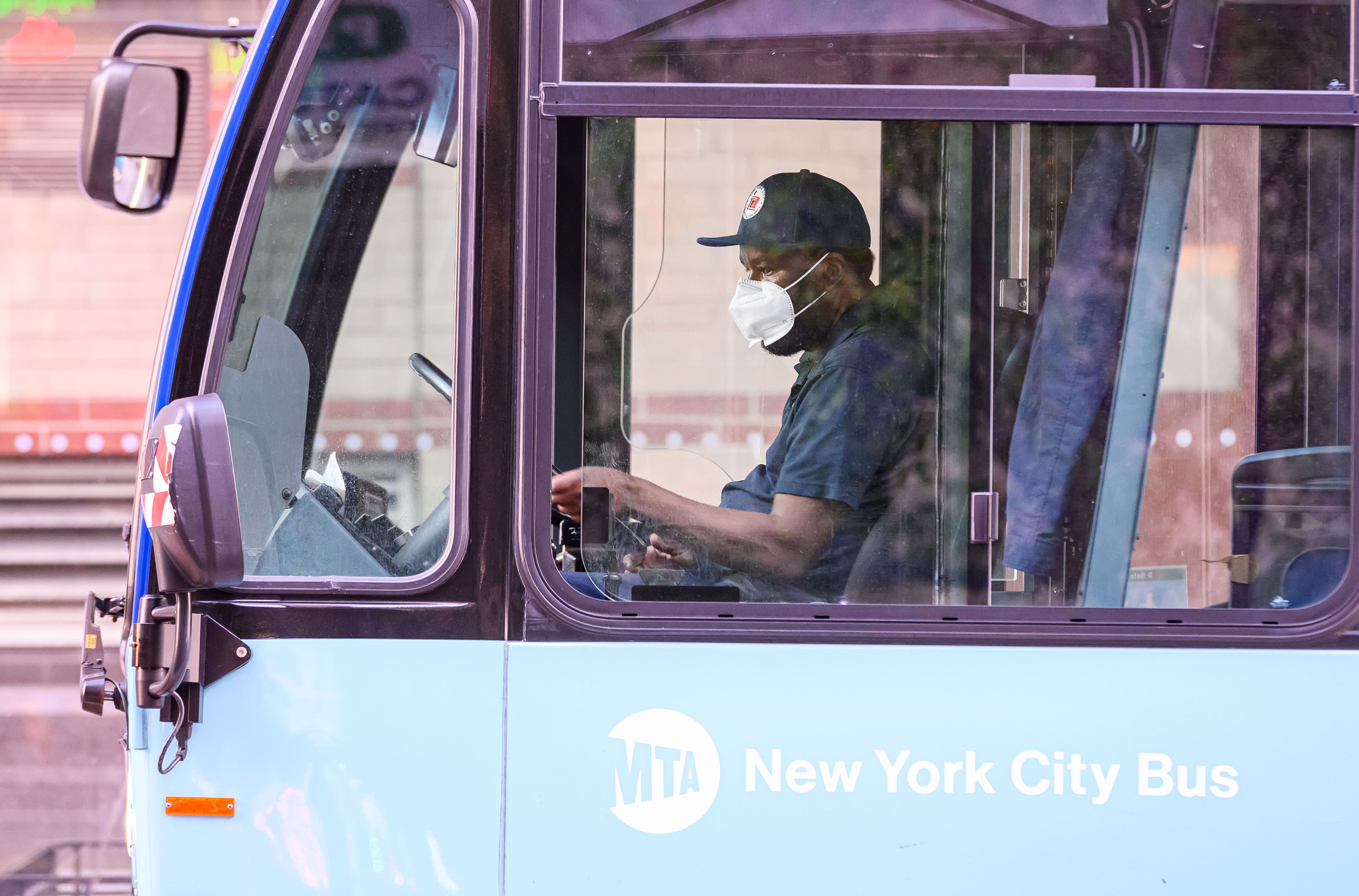 A Black man driving a bus.