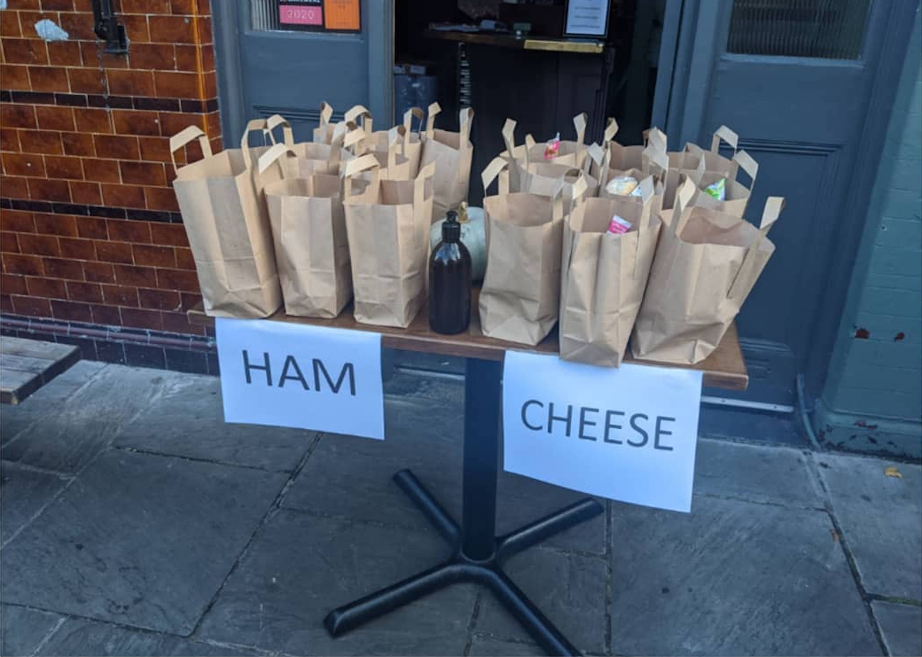 """Paper bags of free school meals made at the Duke of Richmond pub and restaurant on a table, divided in to two sections and labelled as """"HAM"""" and """"CHEESE"""""""