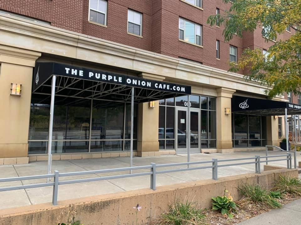 The black awning with white writing at The Purple Onion hangs over a beige sidewalk and large, blank glass windows