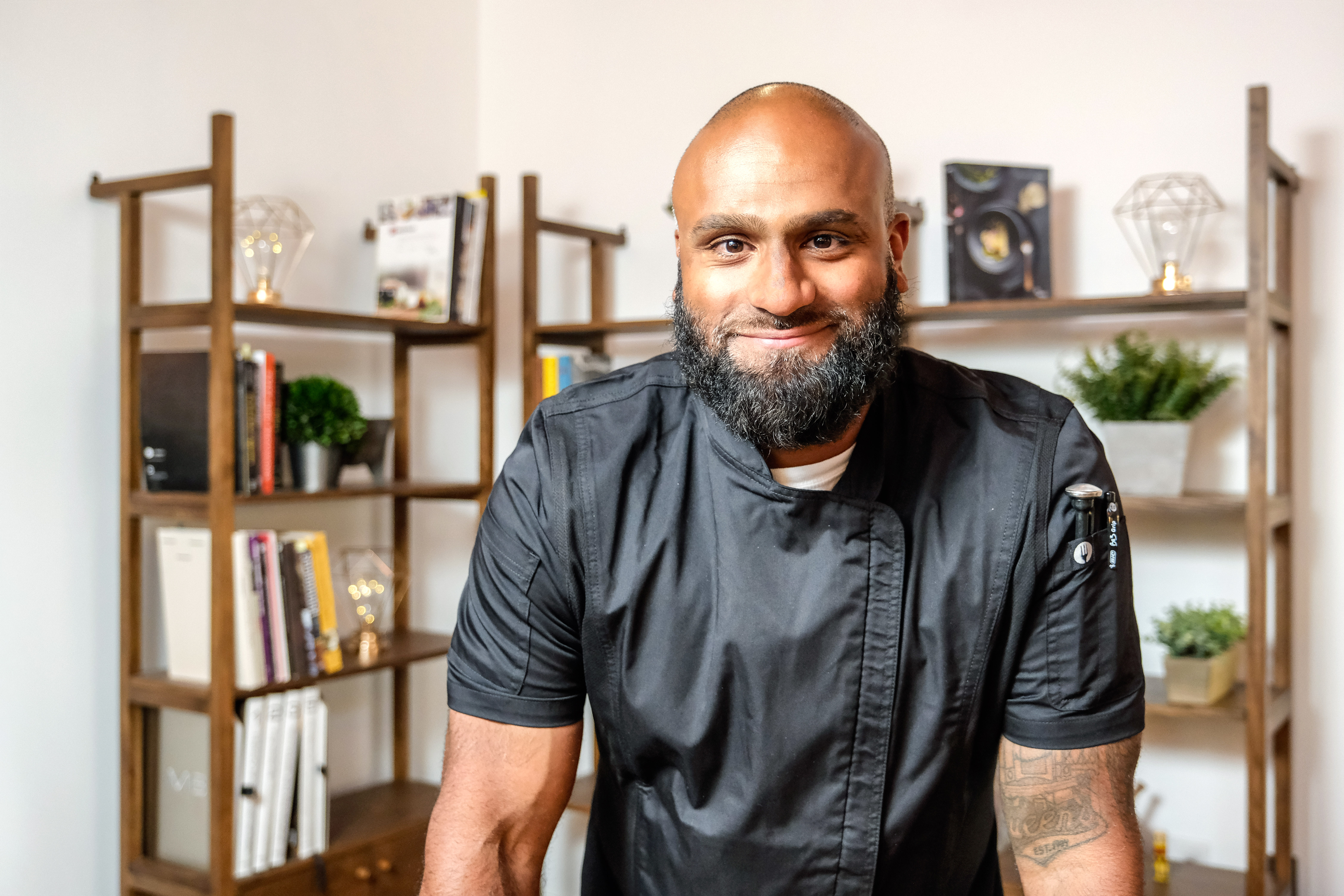 A chef leans forward with bookshelves behind him.