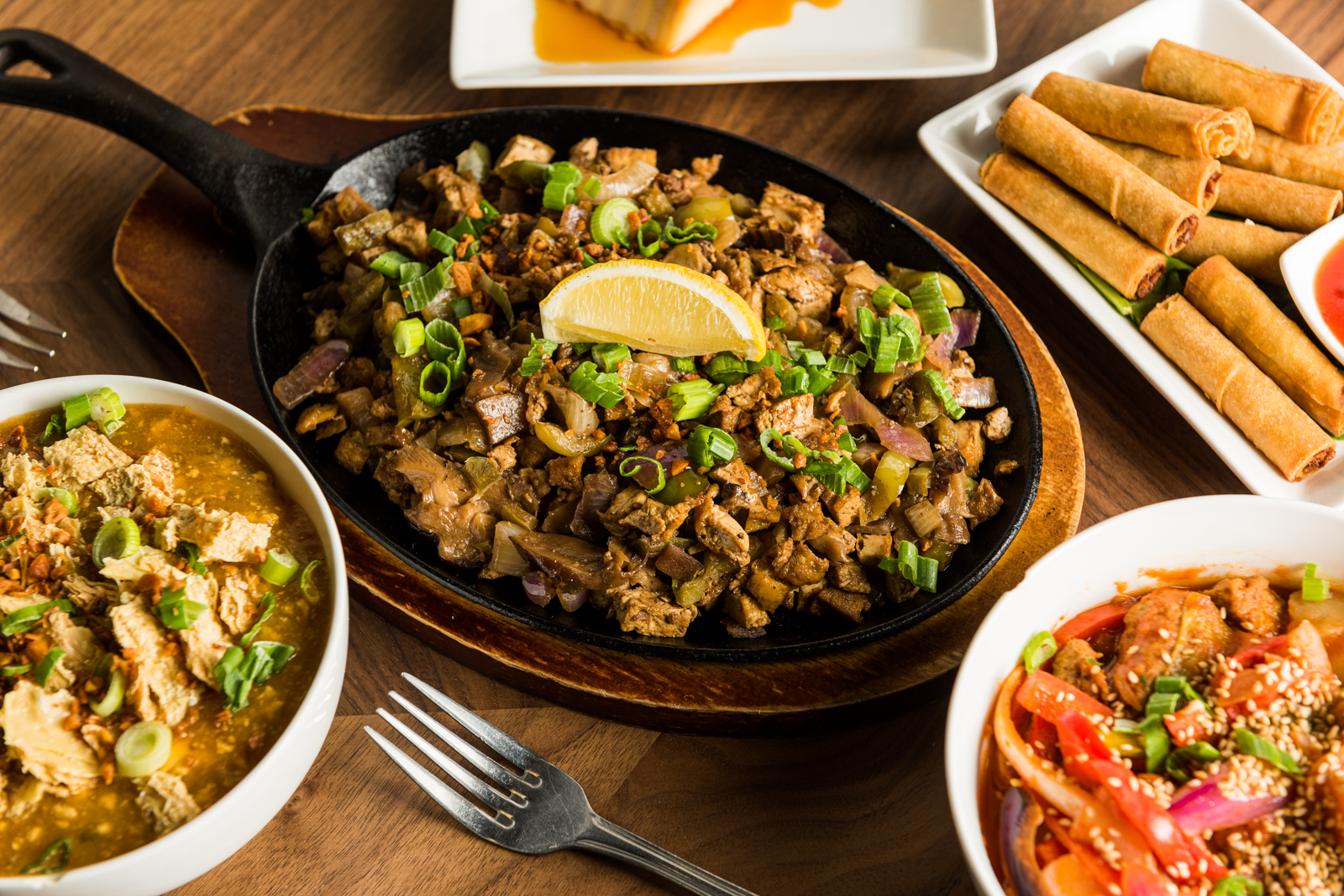 a spread of vegan Filipino dishes including sisig and lumpia