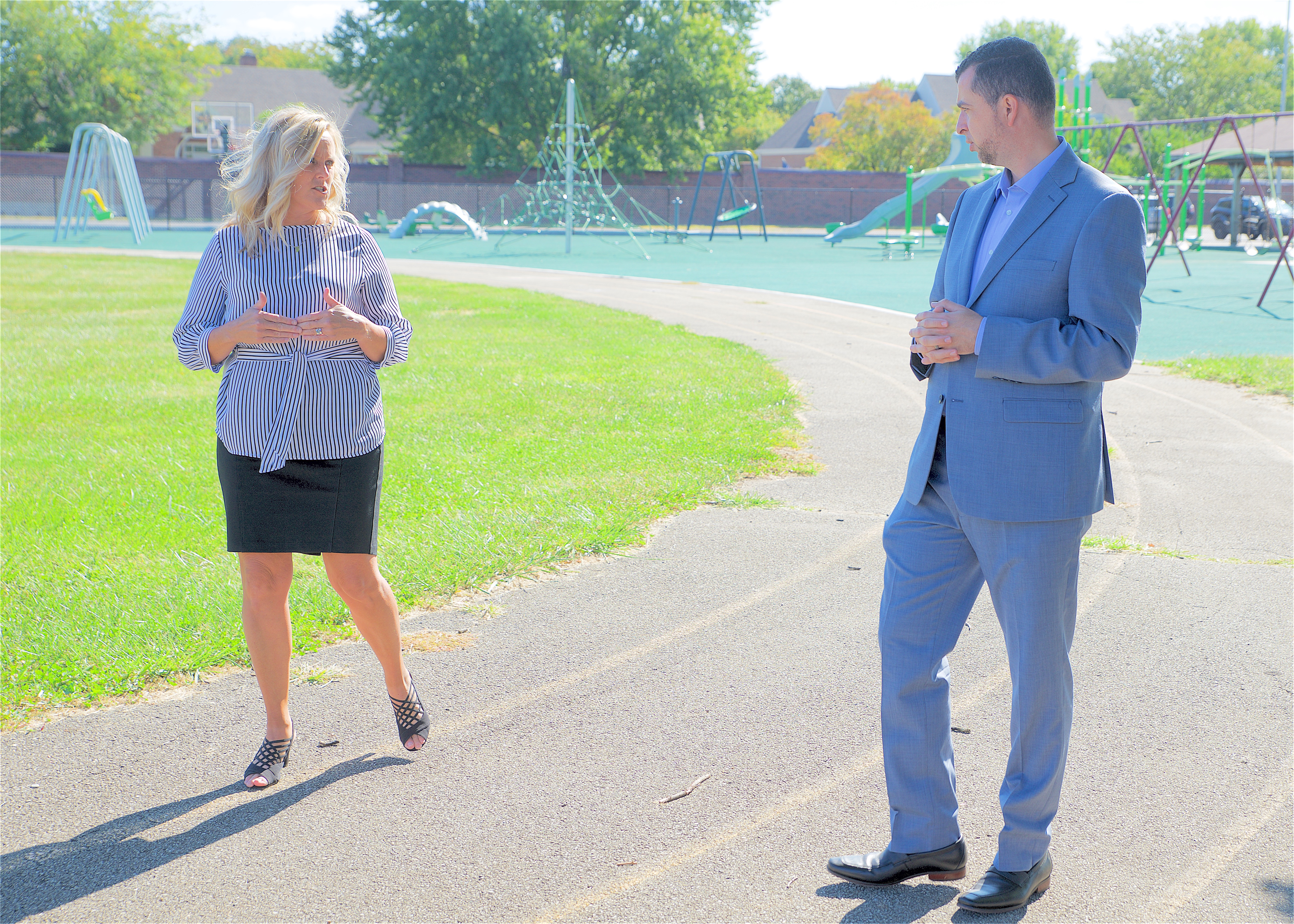 Indiana education chief Jennifer McCormick and Democratic state Senate candidate Fady Qaddoura.walk on a track as part of a political ad.