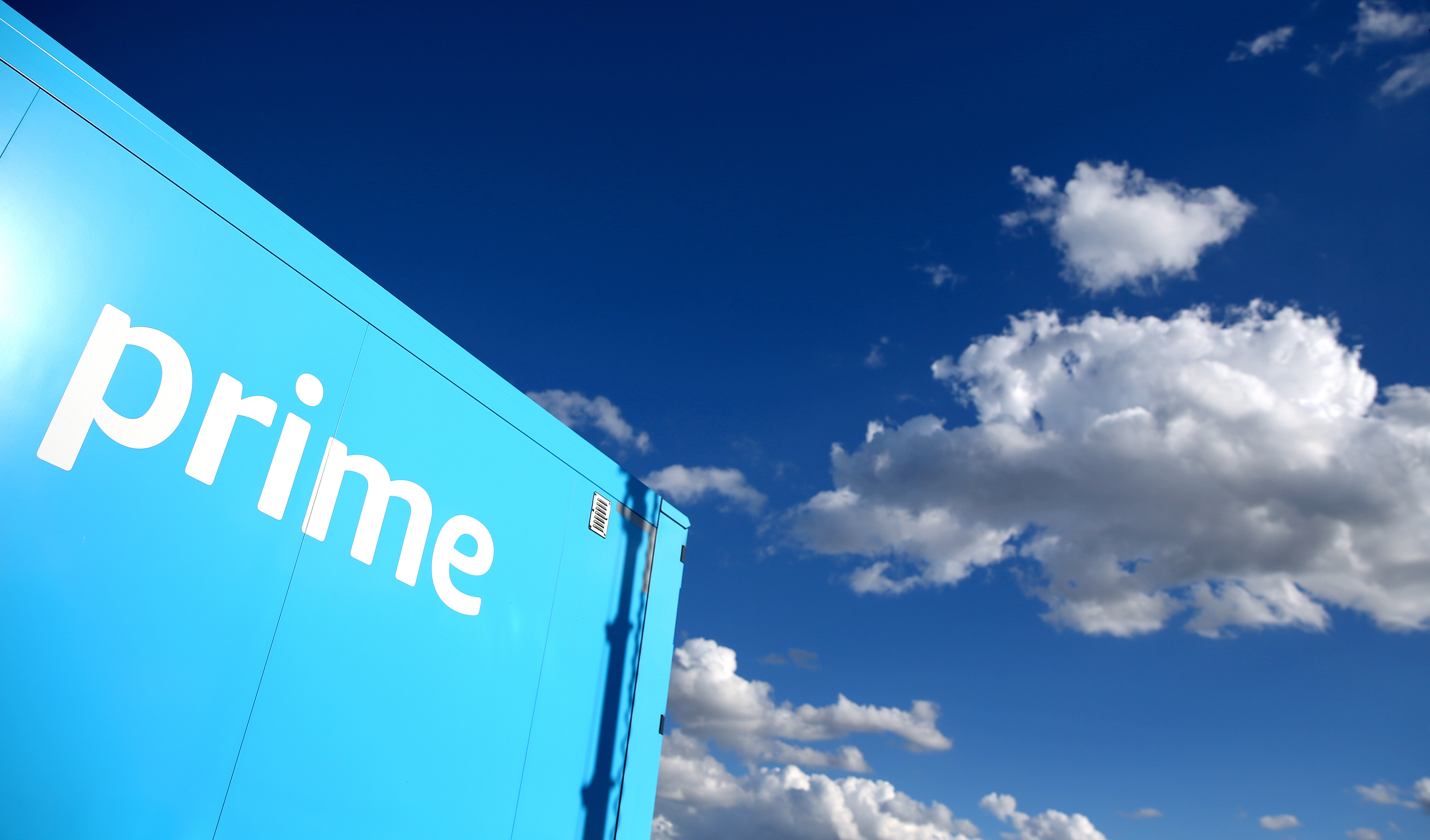 "A corner of a truck with the word ""prime"" on it against a blue sky with white clouds."