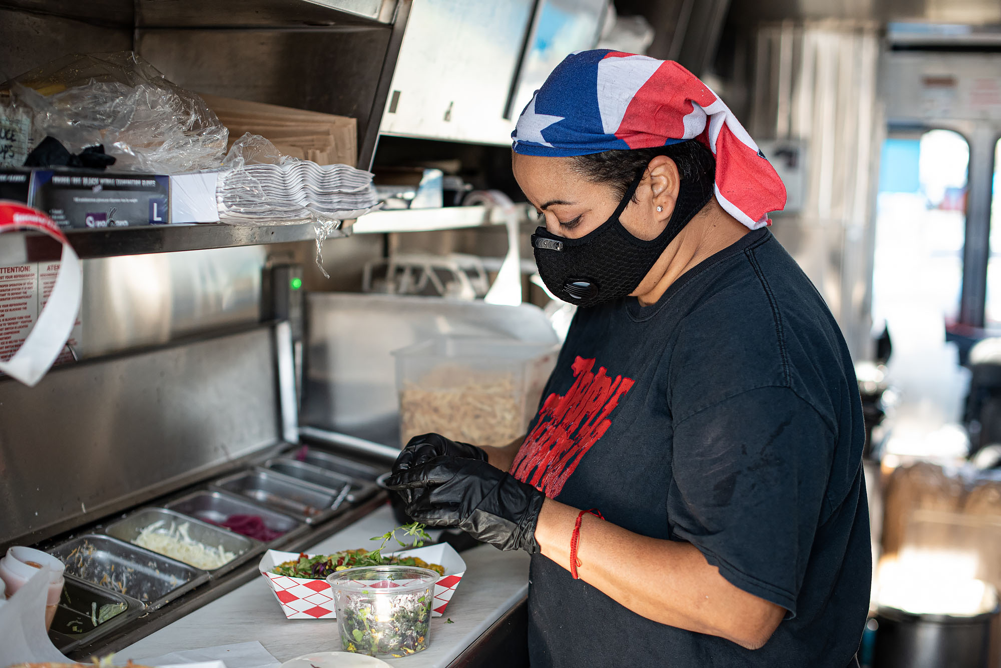 Omayra Dakis of Triple Threat Truck in a food truck kitchen wearing a Puerto Rican flag and mask.