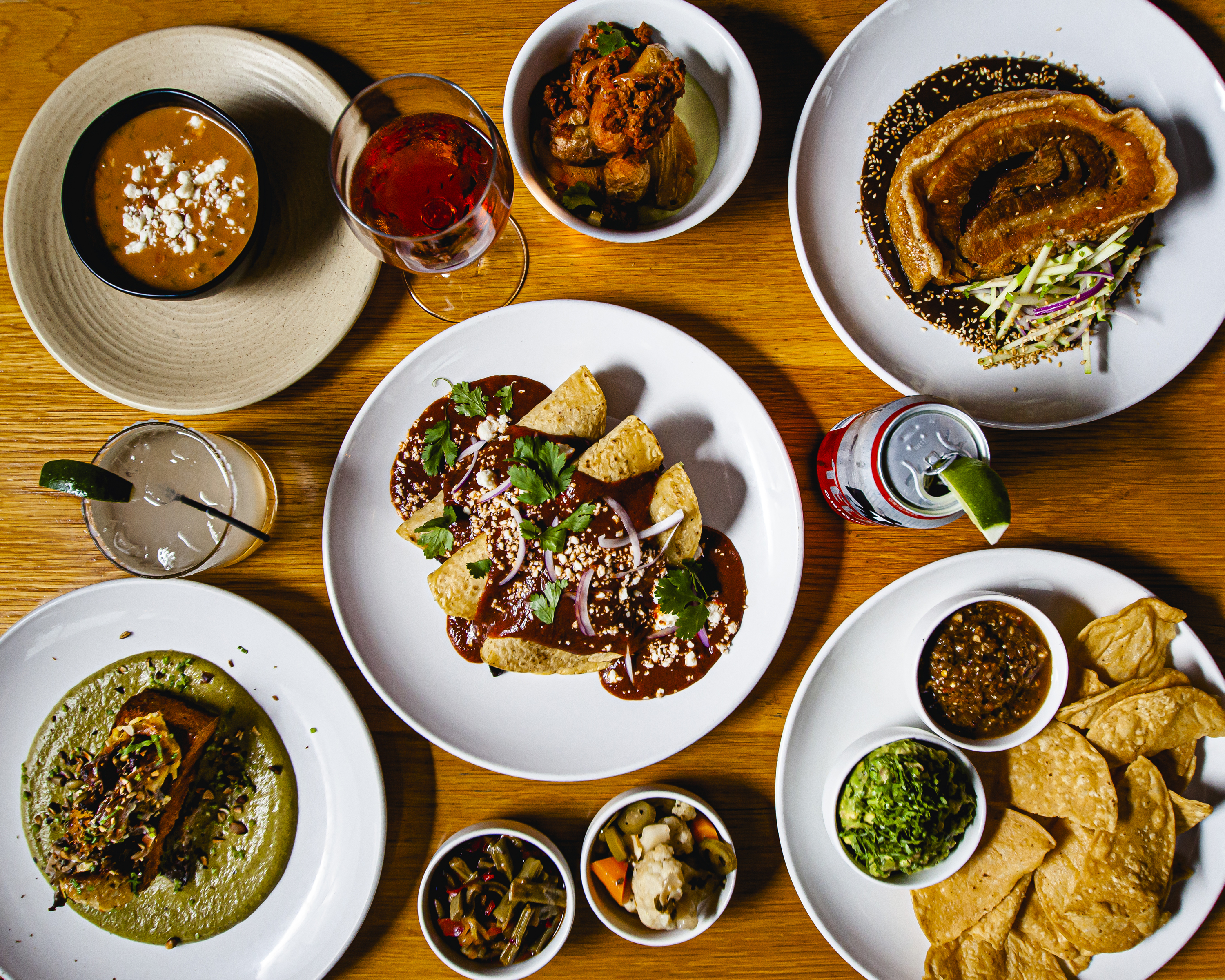 A wooden table filled with round plates and bowls of Mexican food, as well as drinks.