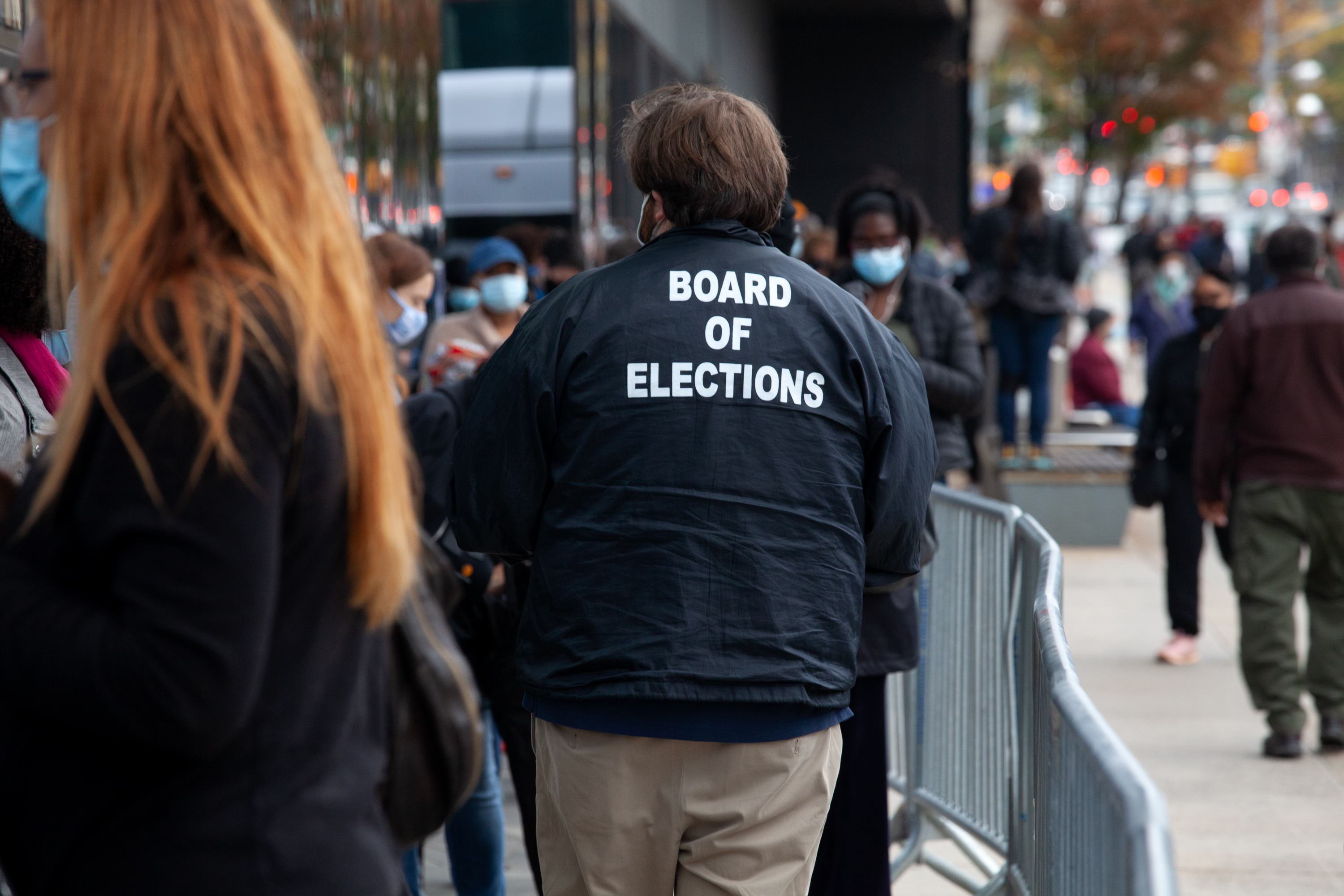A city Board of Elections worker speaks to New Yorkers in long lines outside the Barclays Center on the first day of early voting, Oct. 24, 2020.