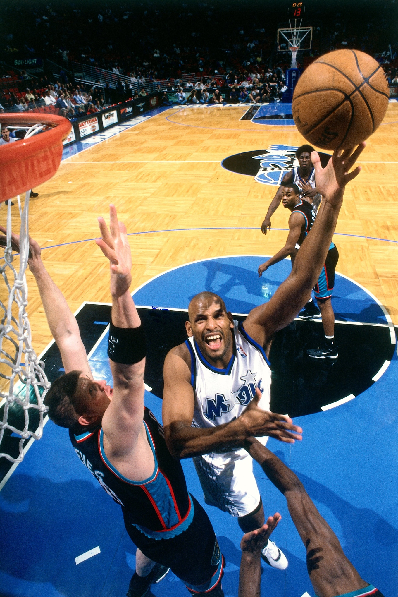 ORLANDO, FL - 2000: John Amaechi #13 of the Orlando Magic shoots against Bryant Reeves #50 of the Vancouver Grizzlies during a game played in 2000 at the TD Waterhouse Center in Orlando, Florida.