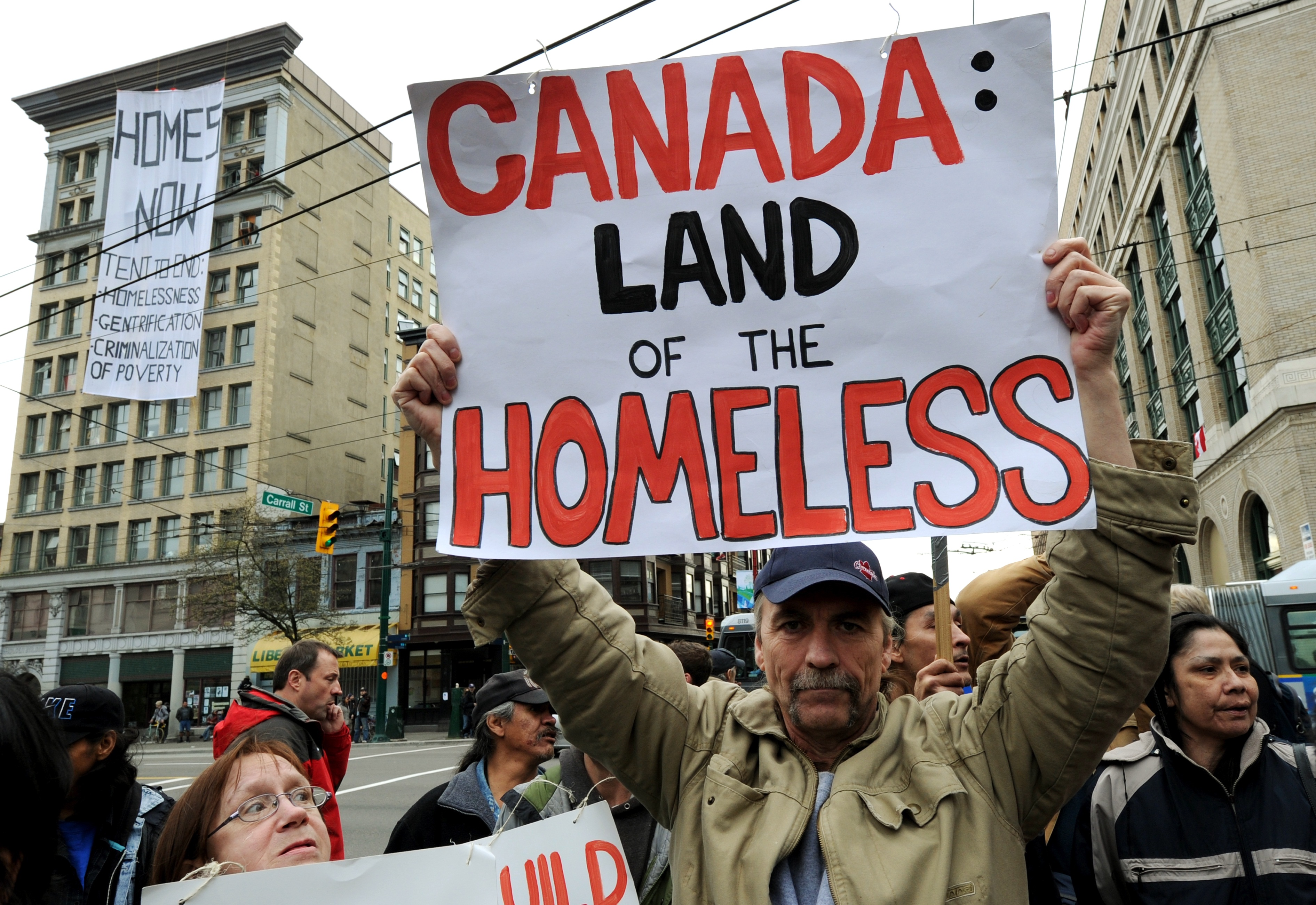 A man holds a sign reading Canada: Land of the homeless.