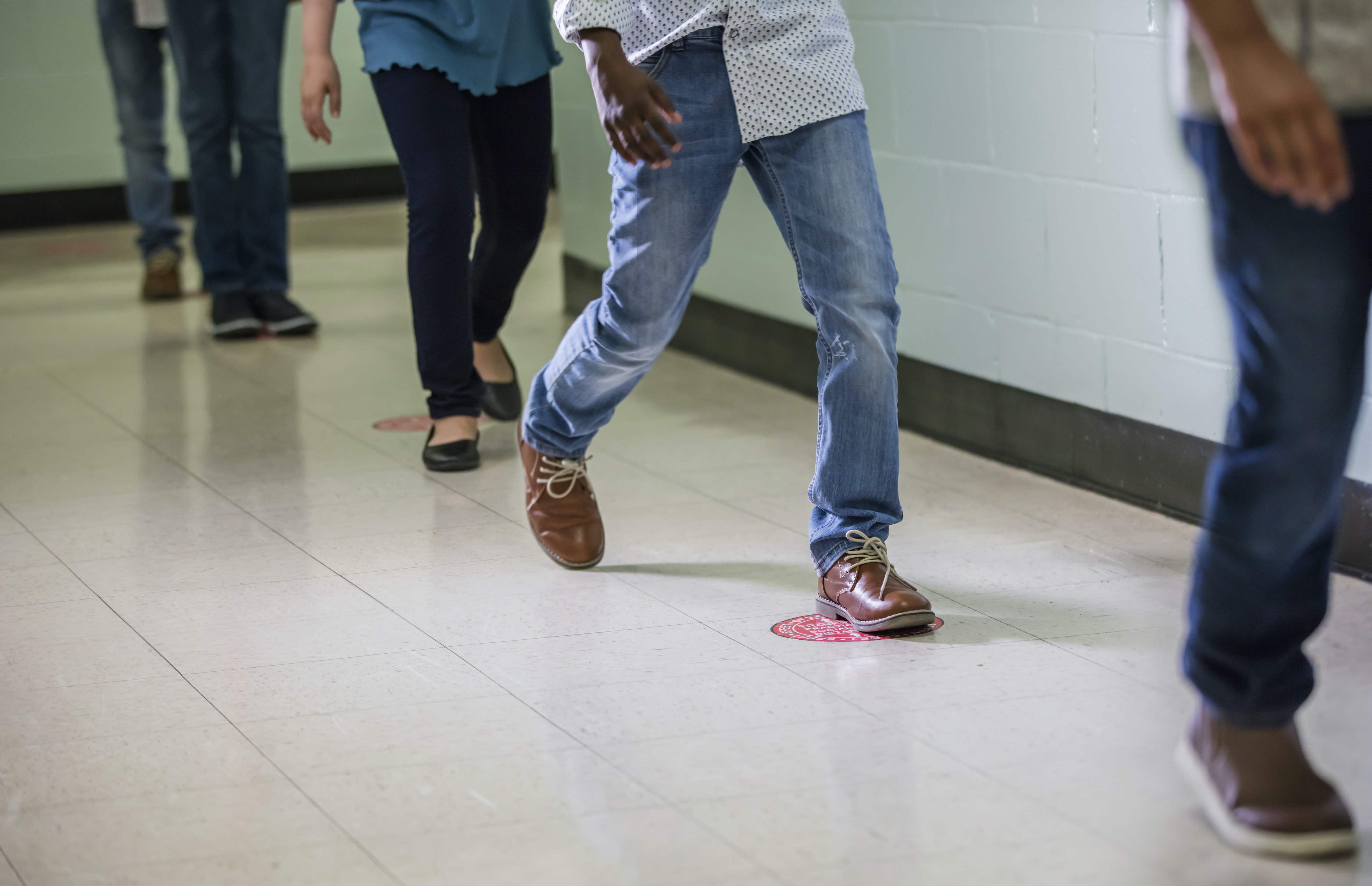 Cropped view of elementary students walking single file in a school hallway.