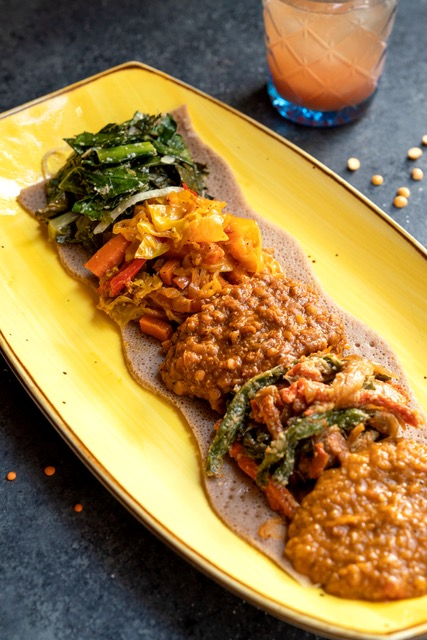 A yellow plate with multi-colored vegetables and lentils placed on it in a row.