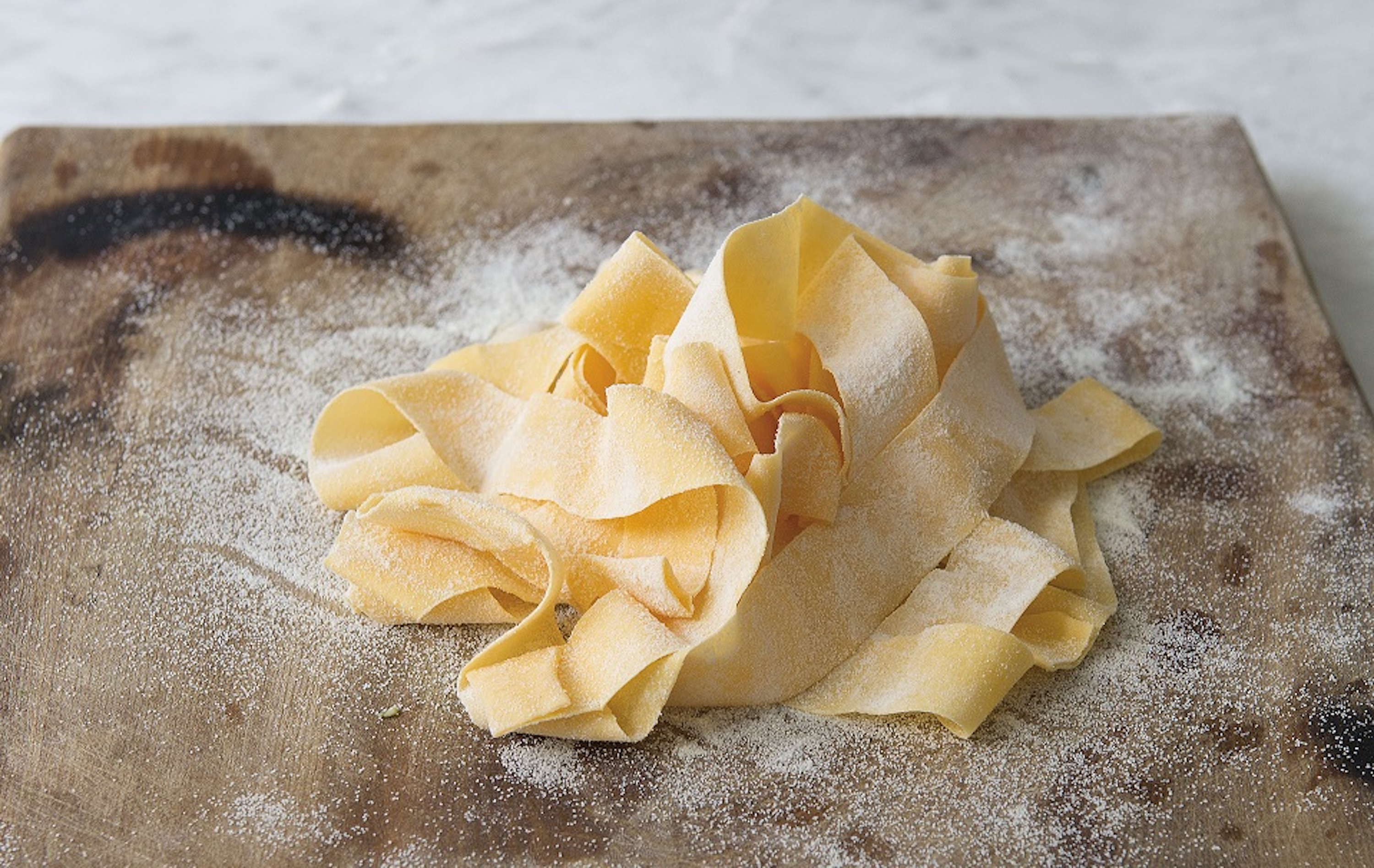 Uncooked fresh pappardelle on a chopping board with a marble background