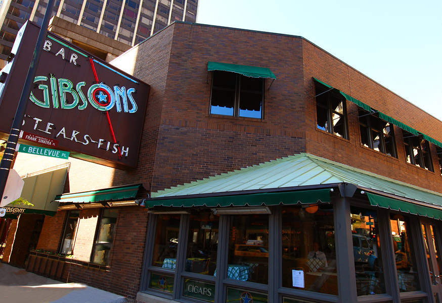 """A brick building with a green roof attachment and a neon sign that reads """"Gibsons."""""""
