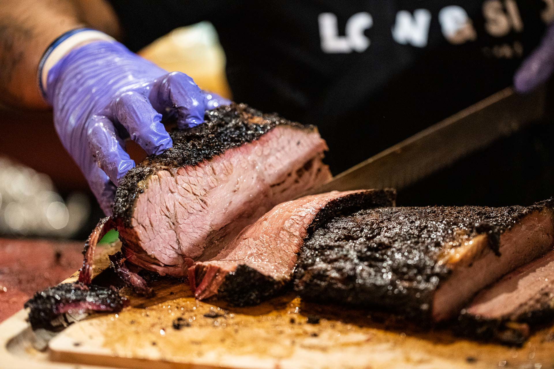 A gloved worker cuts slices of brisket on a wooden counter at Jack's BBQ