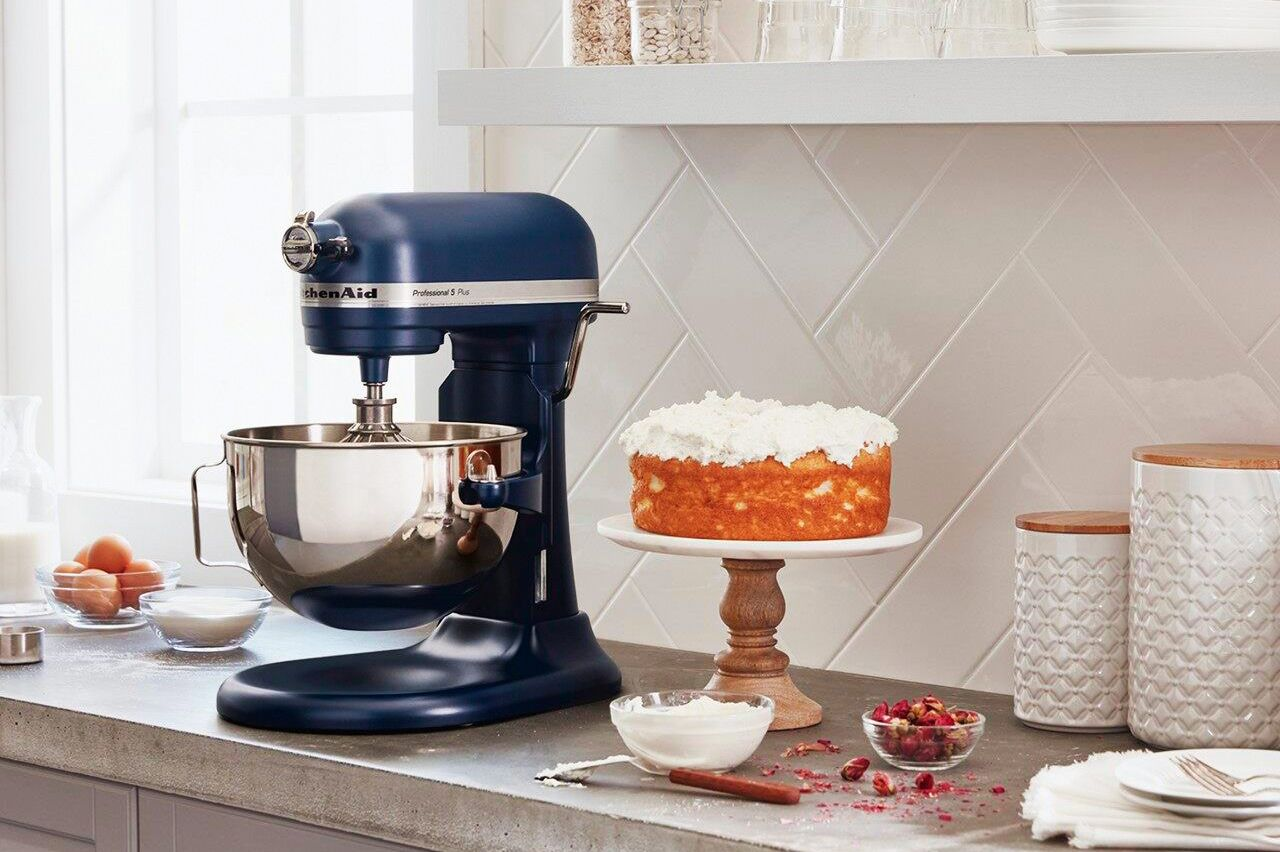 A KitchenAid mixer on a counter next to a cake on a cakestand