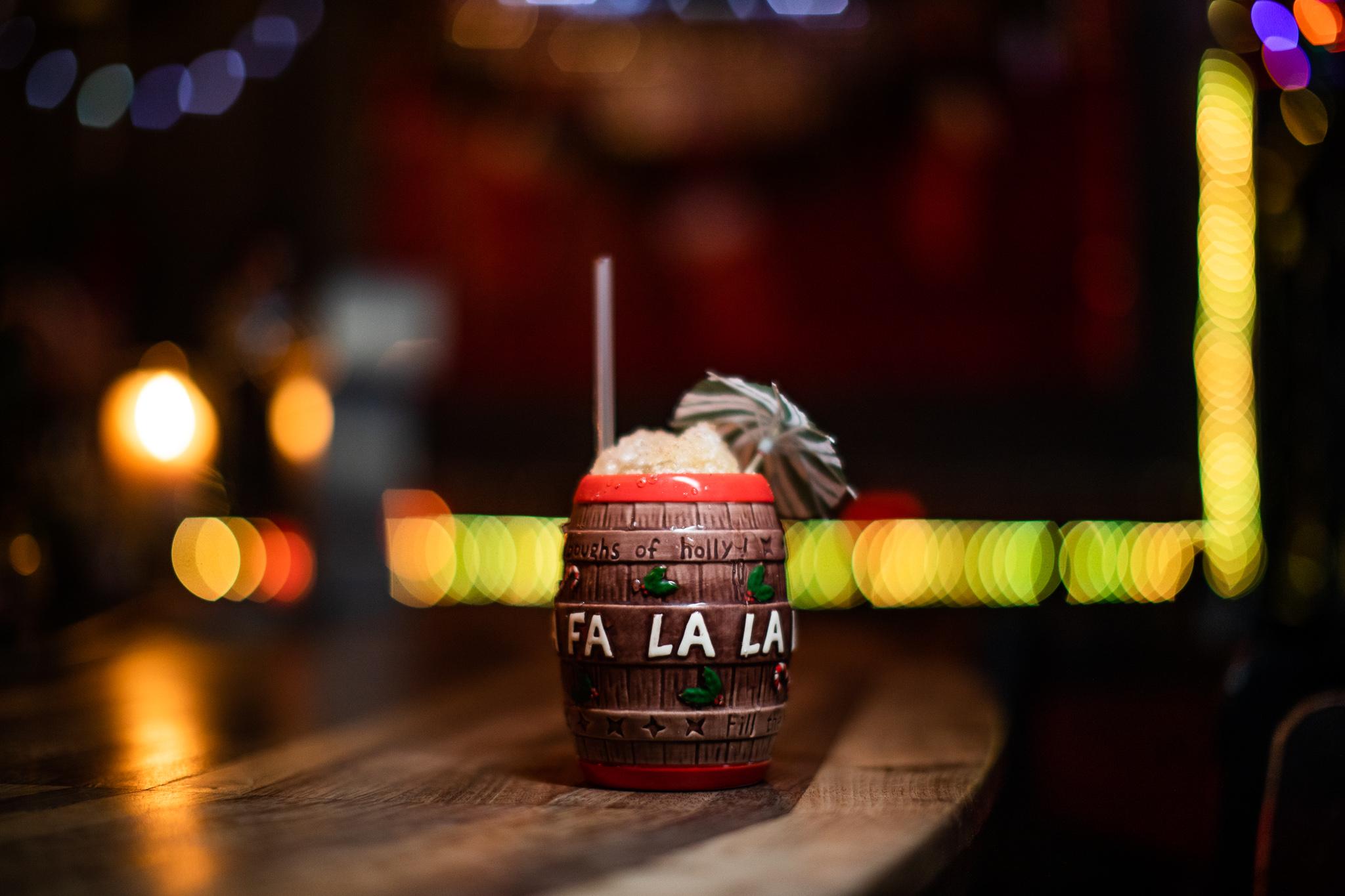 A cocktail on a bar in a decorative barrel mug that reads Fa La La La La.