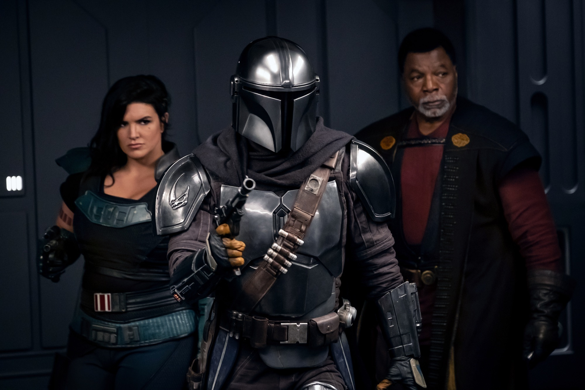 Cara Dune, The Mandalorian, and Greef Karga stand in an elevator with their blasters up