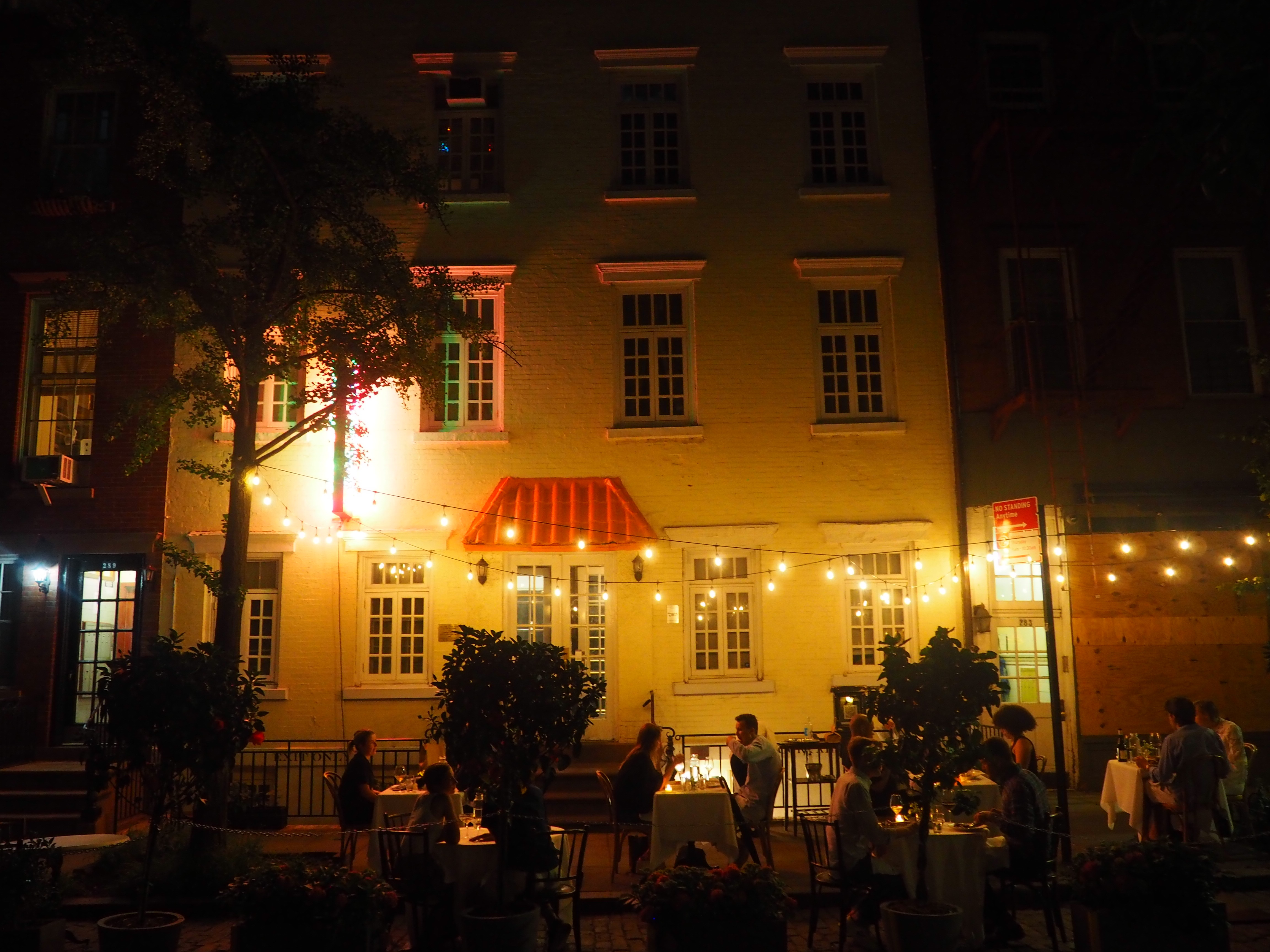 Outdoor dining in front of a restaurant at night with lights strung up around the outdoor tables