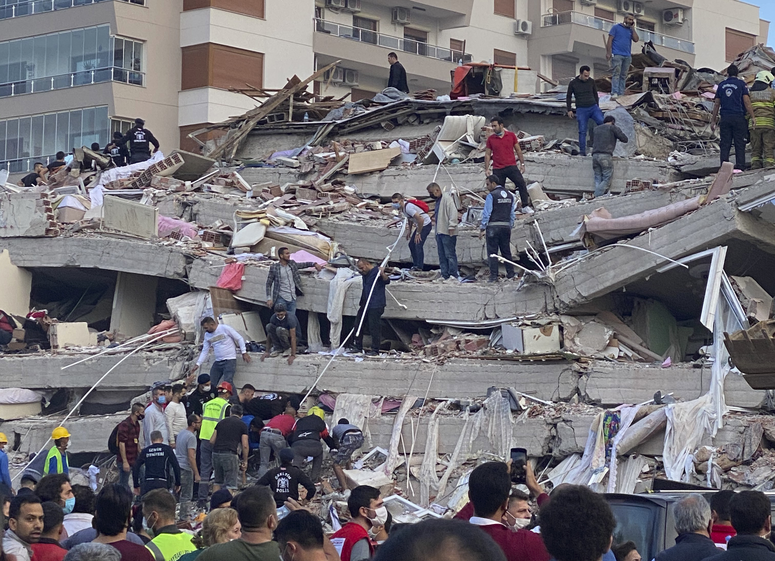 Rescue workers and others try to save people trapped in the debris of a collapsed building, in Izmir, Turkey after a deadly earthquake Friday in the Aegean Sea rocked western Turkey and the Greek island of Samos. It was also felt in Athens and in Bulgaria.