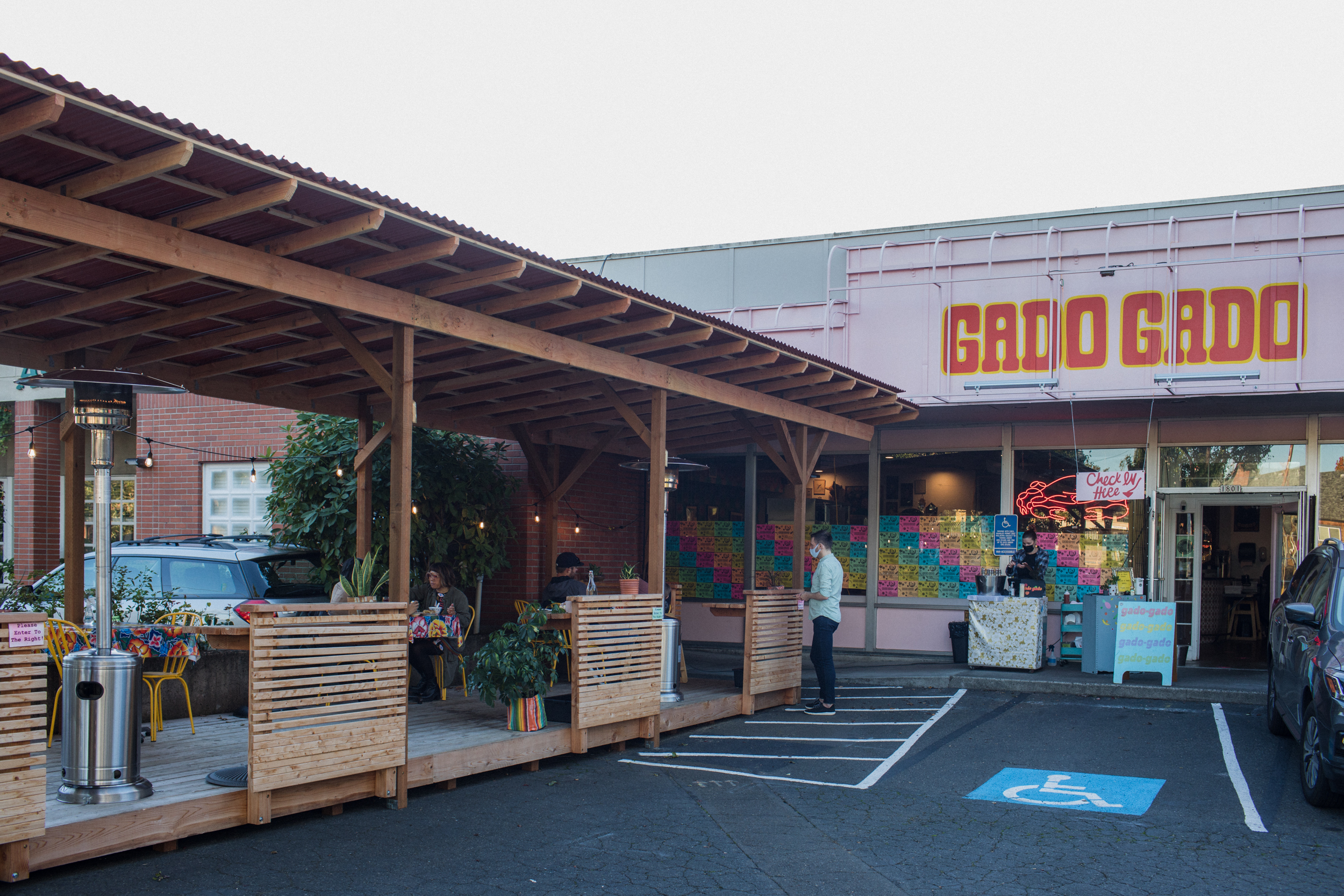 The outside of a restaurant, Gado Gado, with a deck of outdoor seating to the left of the entrance