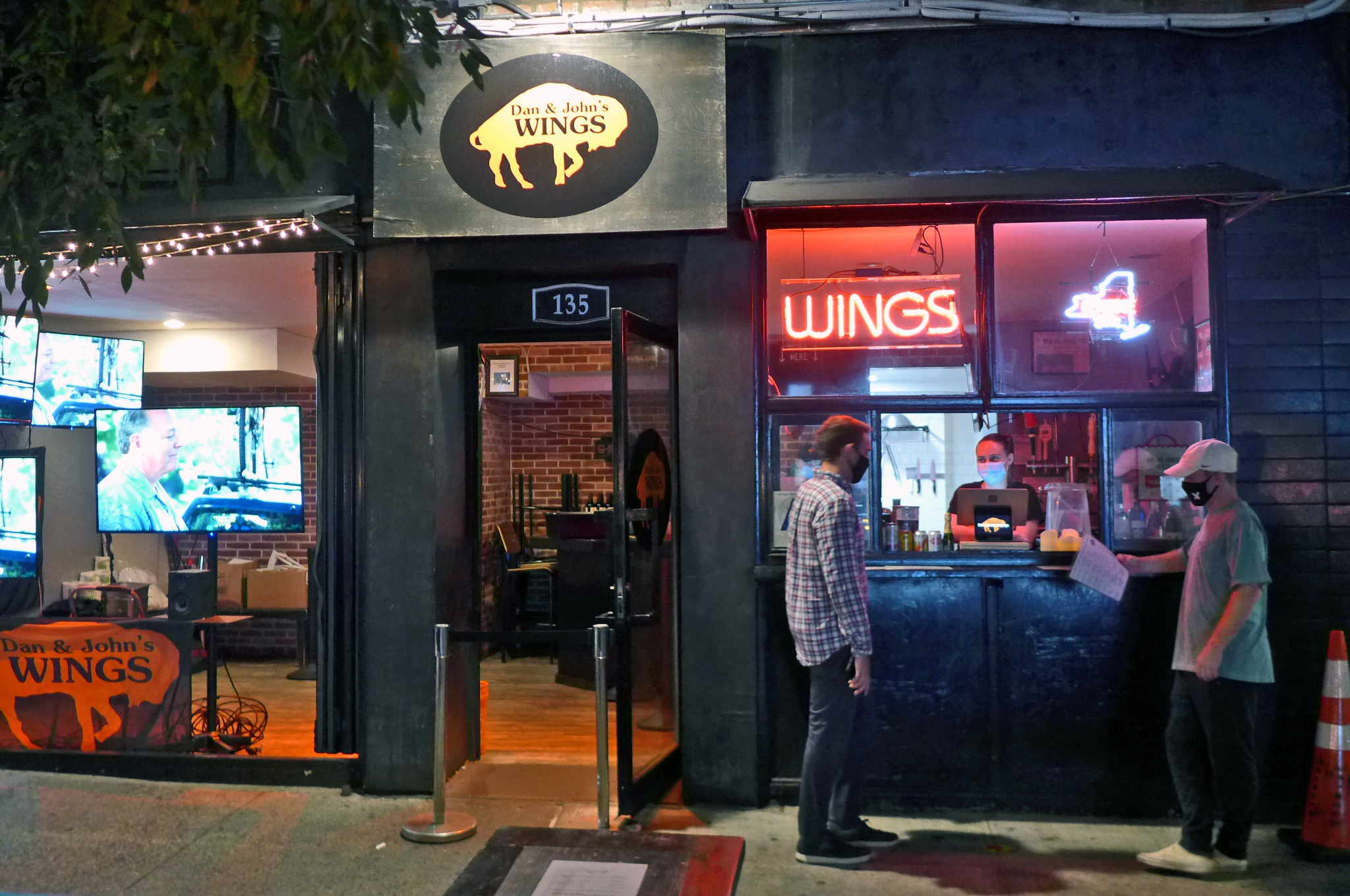 A darkened storefront with a few masked customers and a neon sign Wings.