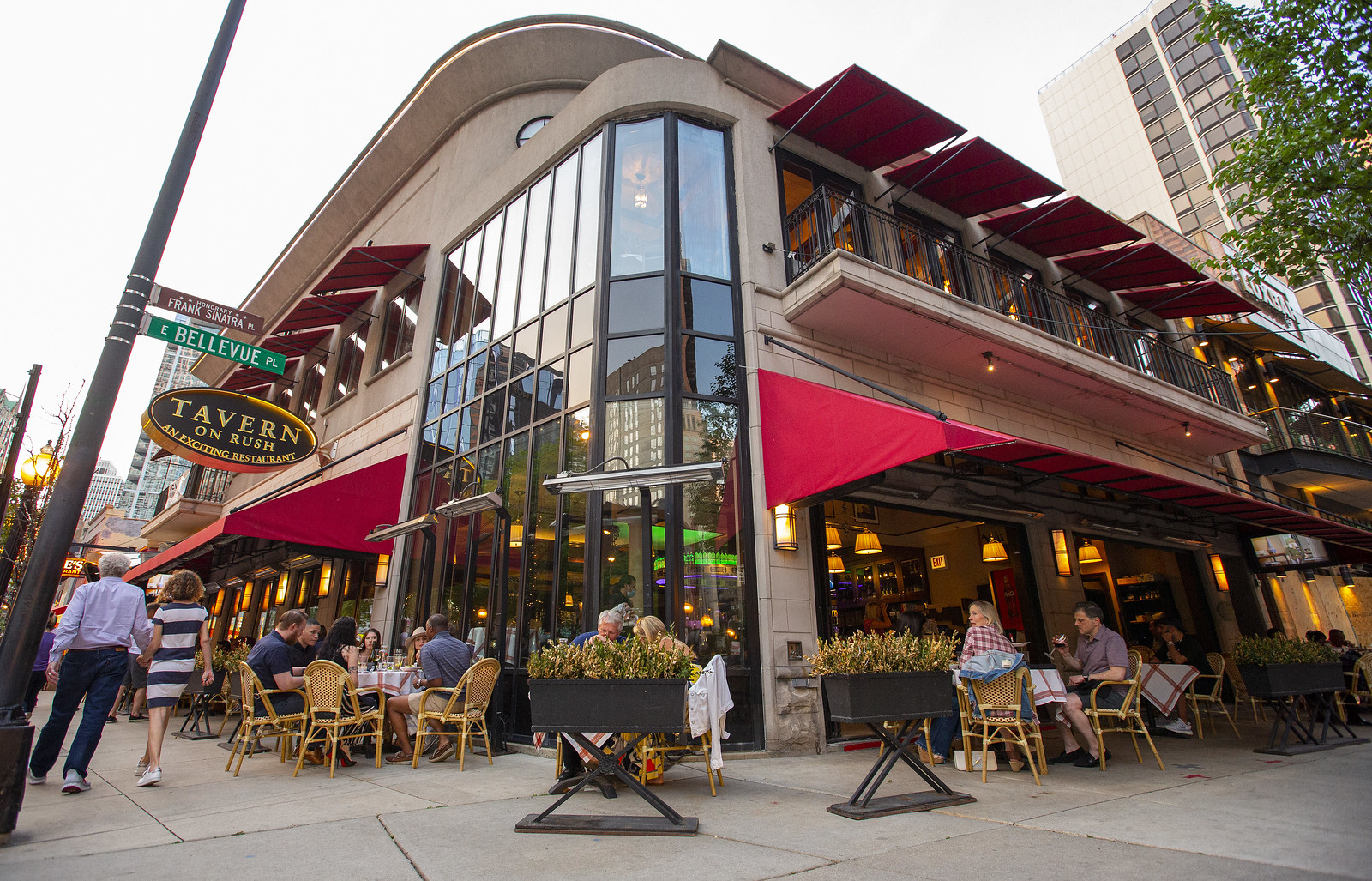 The exterior of Tavern on Rush, with several folks dining outdoors.