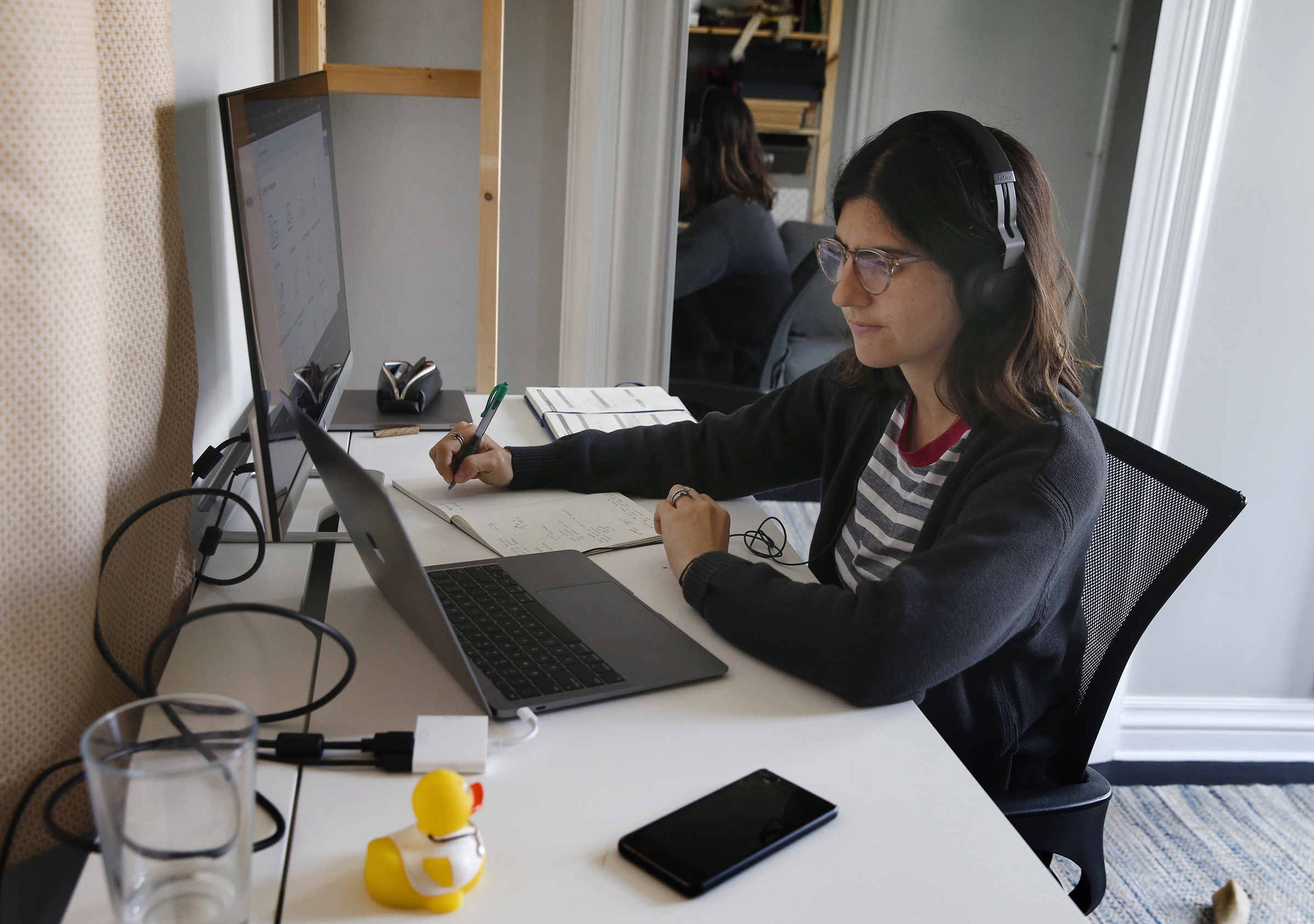 A person wearing headphones sits at a desk with a laptop computer and a flatscreen.