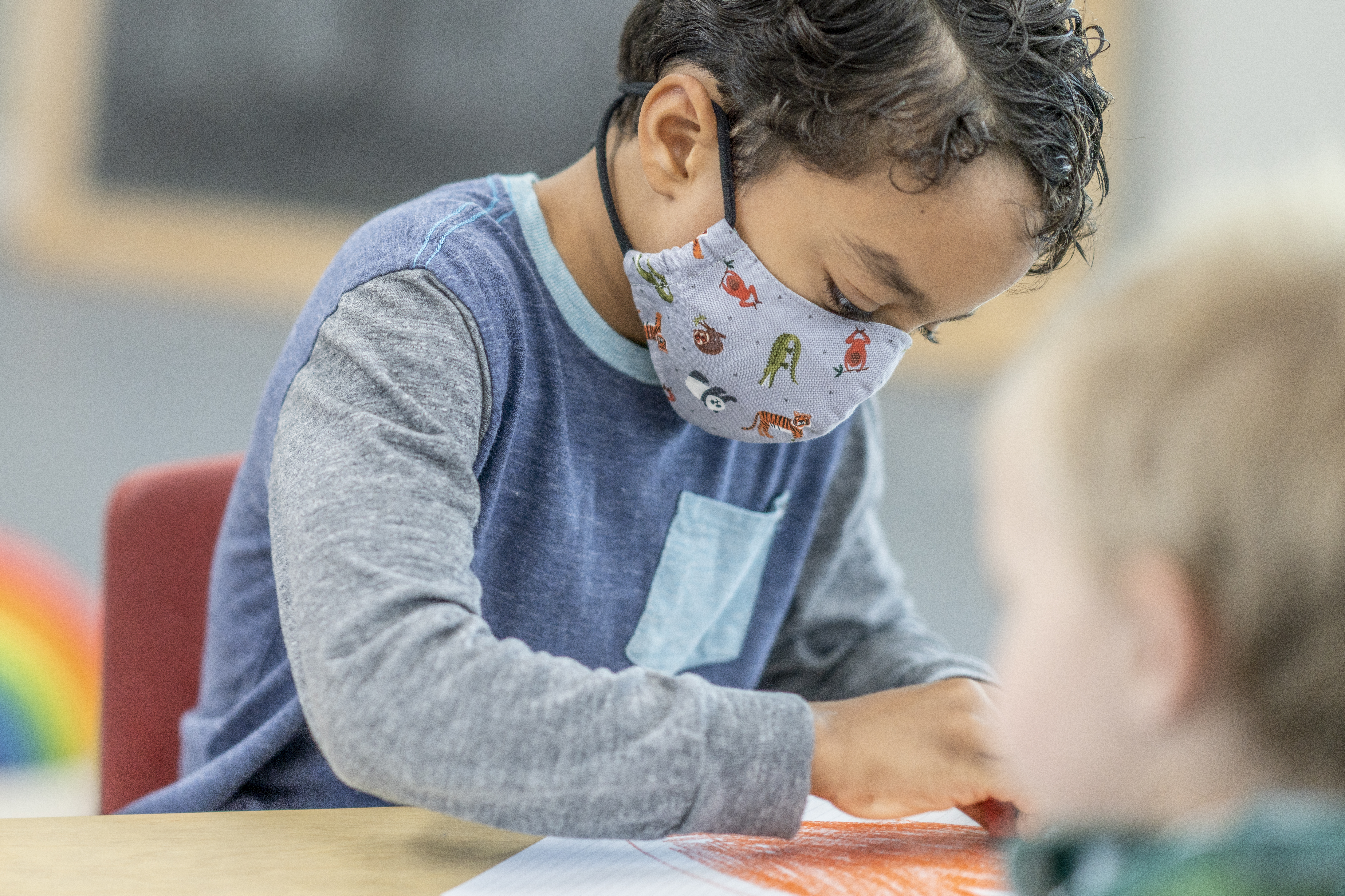 A child in a mask at a day care colors
