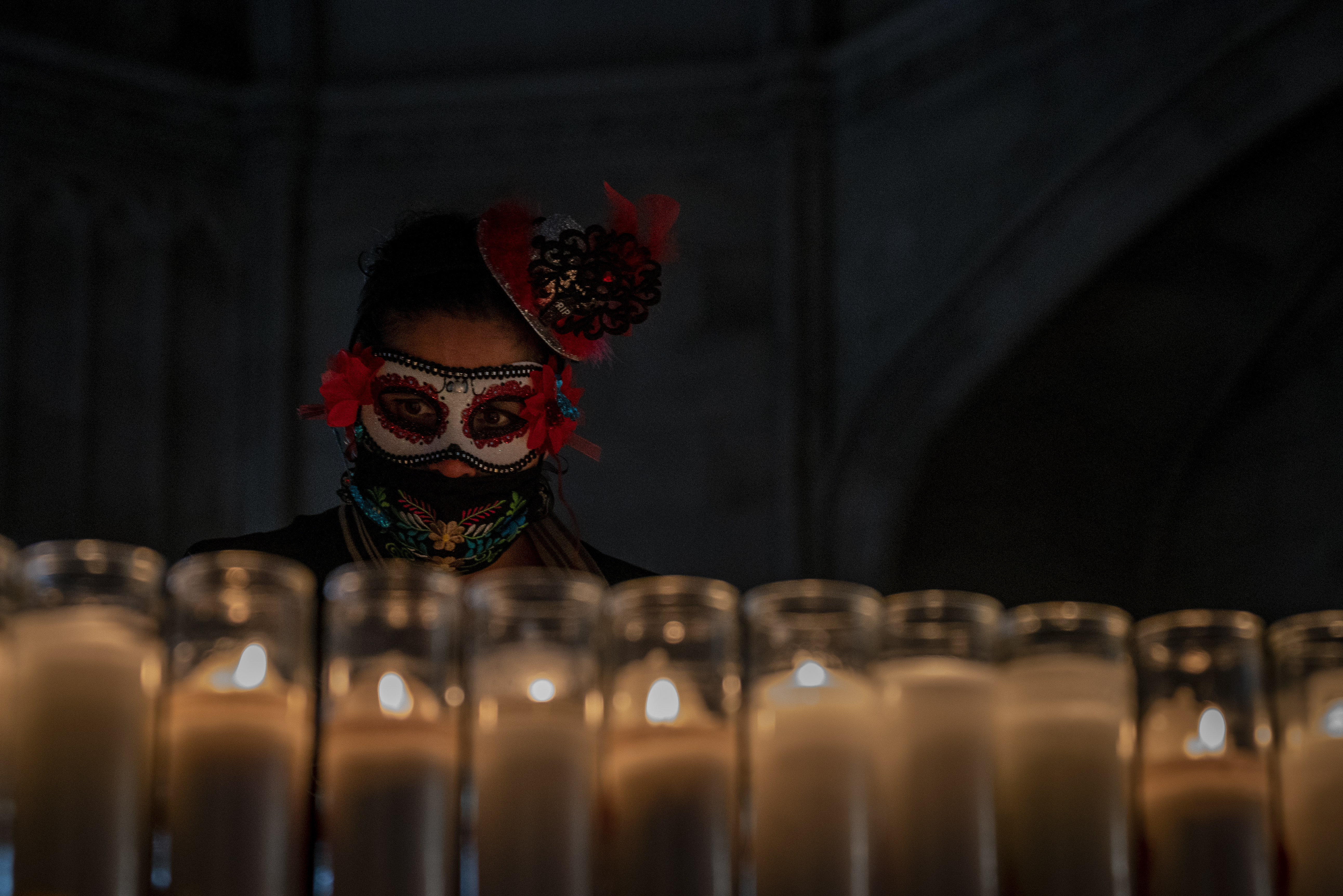Lorie Erlitz-Pagdon, 47, lights a veladora in memory of her family at the Green-Wood Historic Chapel, Oct. 25, 2020.
