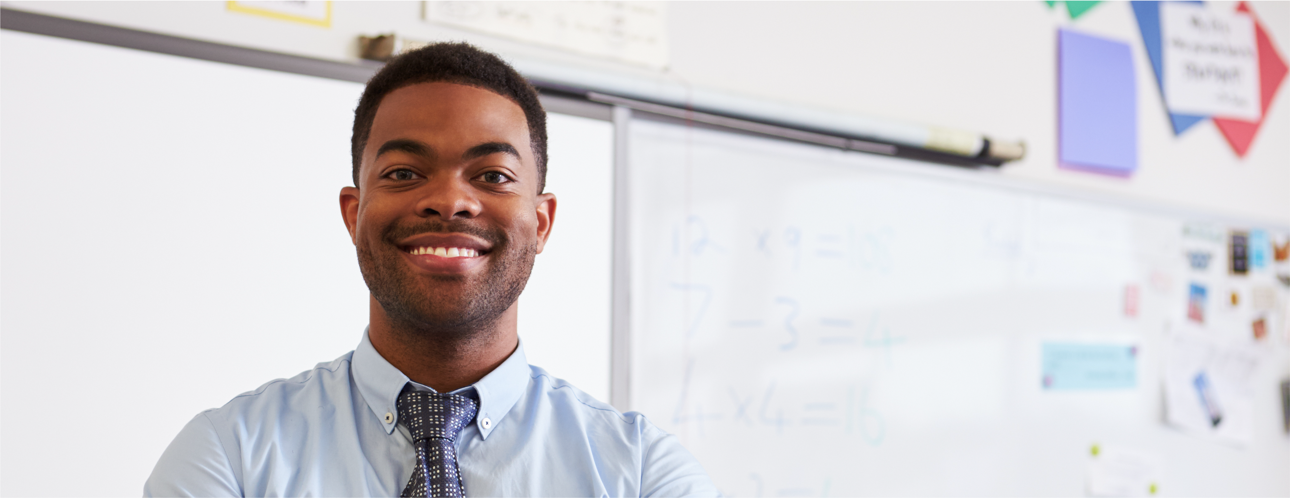 A teacher smiles and stands in front of a whiteboard in his classroom.