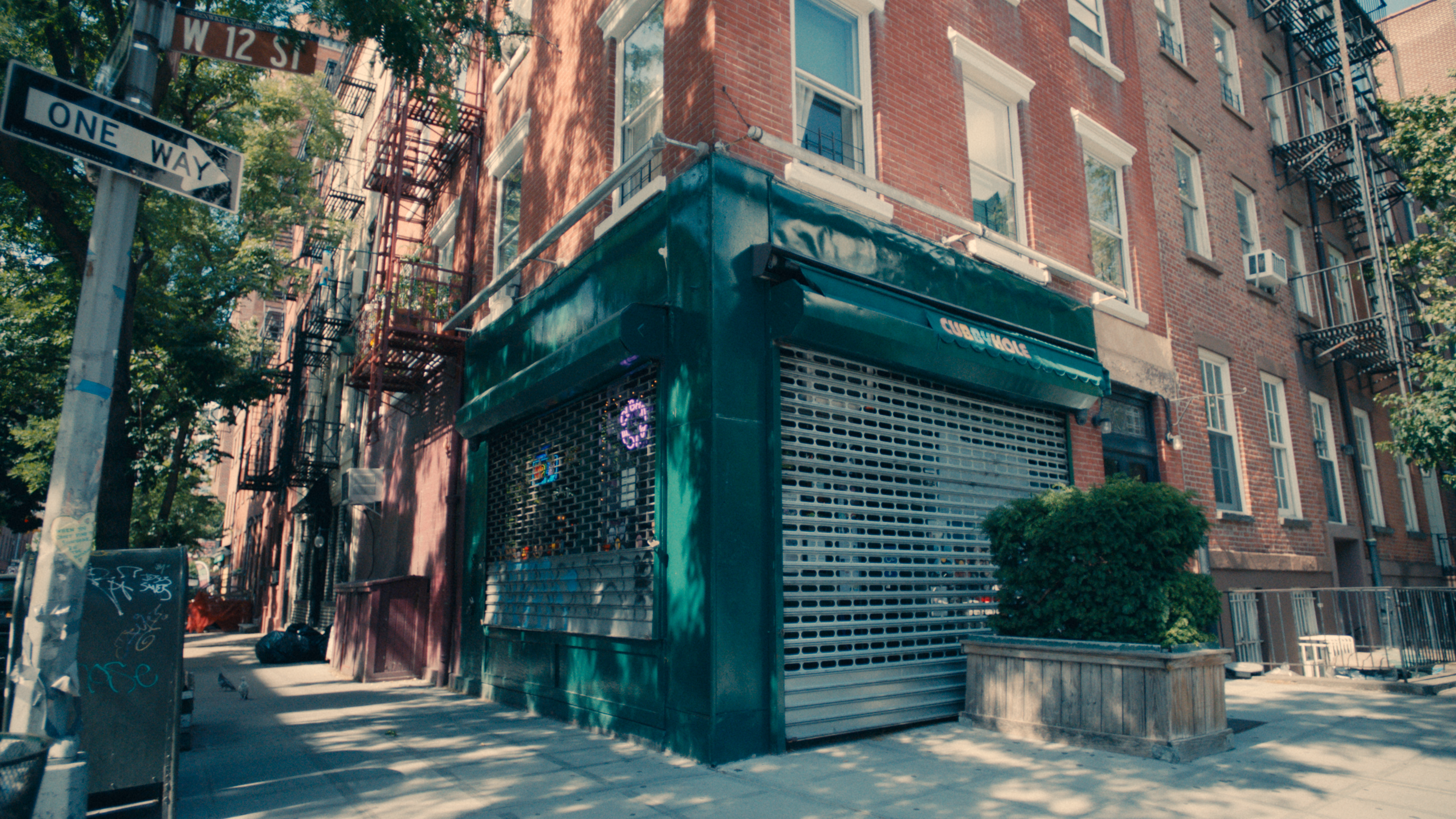 A bar with green trim, neon signs, and its security gate down on a block in New York's West Village.
