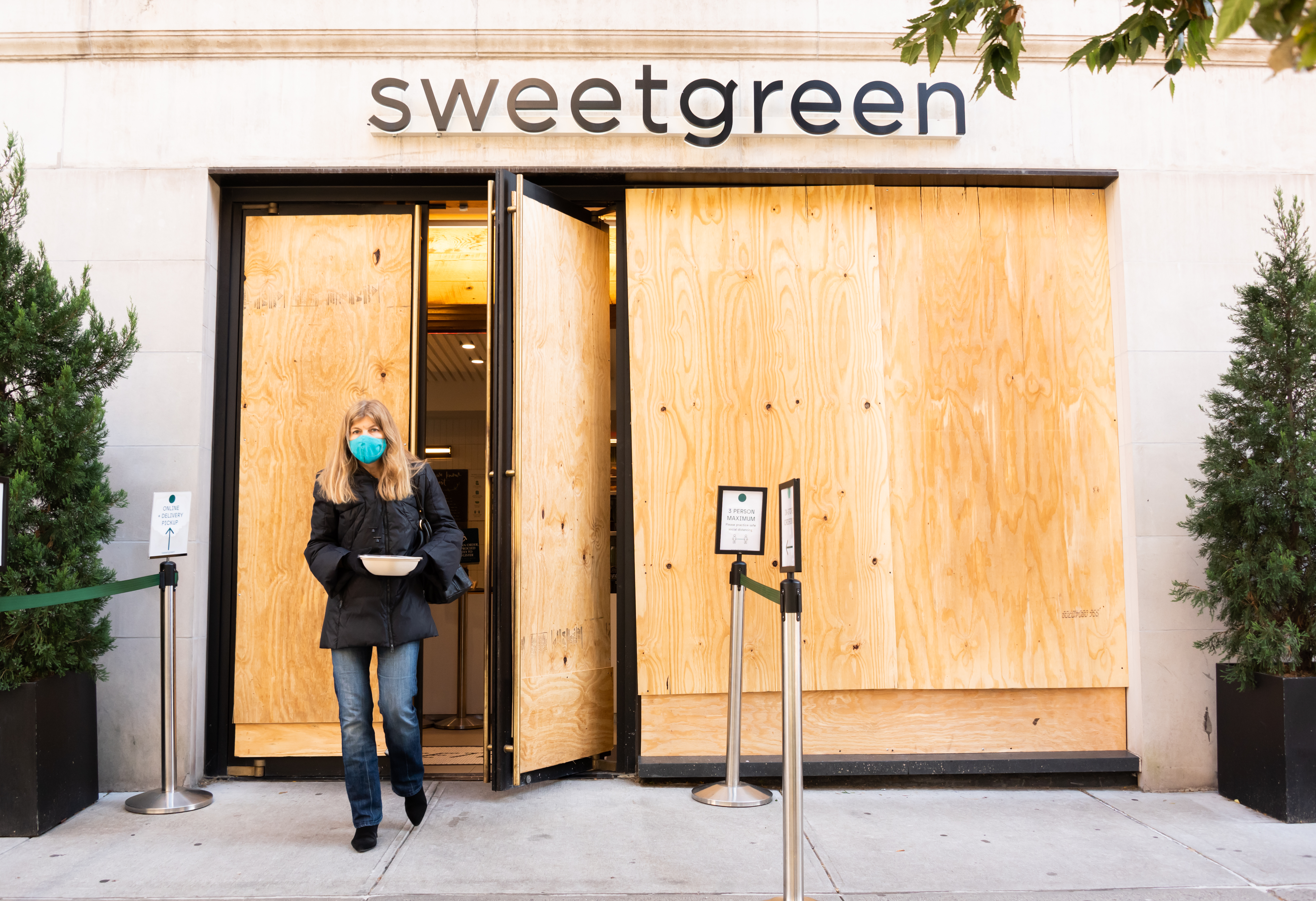 A masked woman walking out of a Sweetgreen with plywood covering the door and the window.