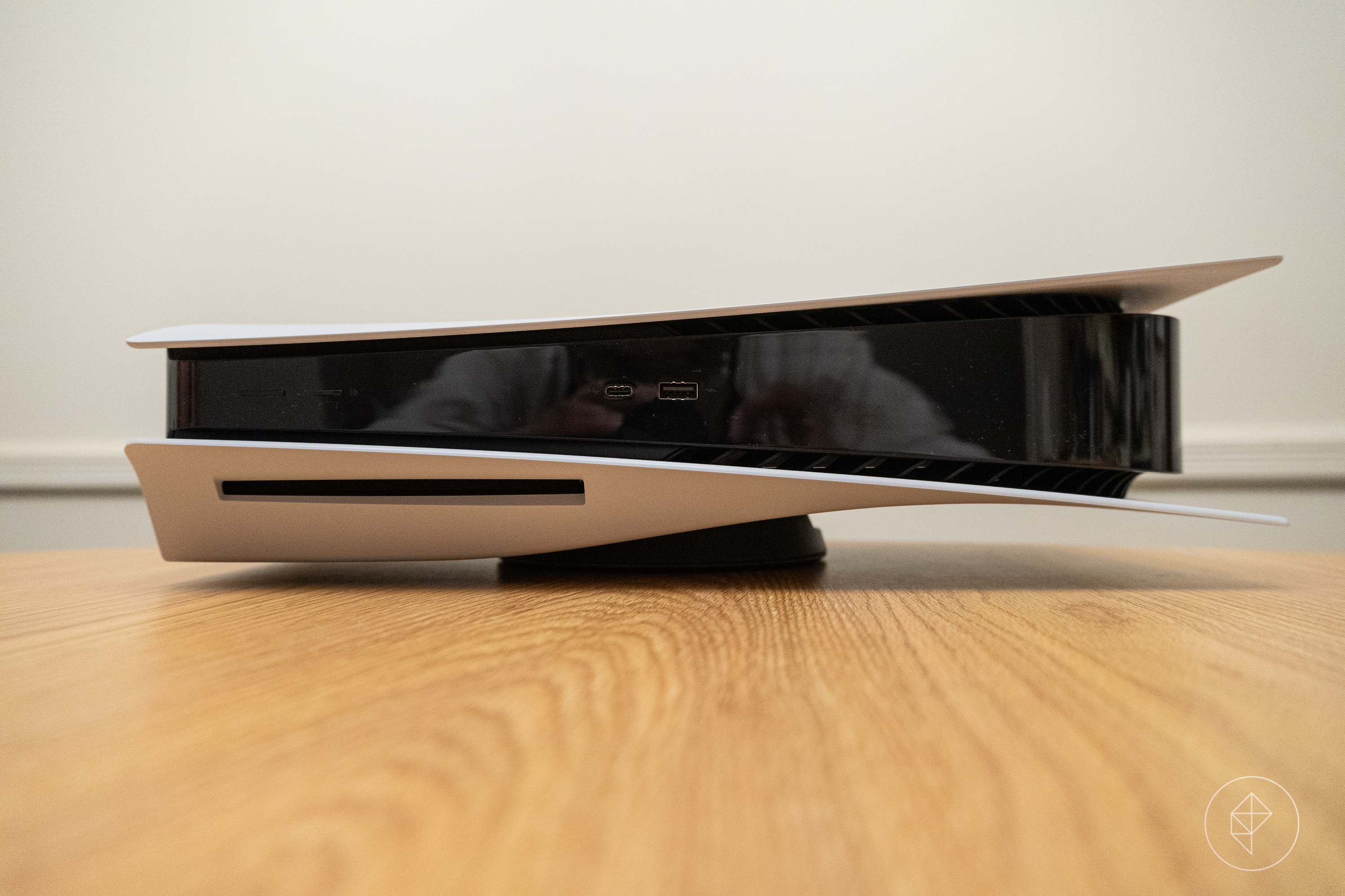 the PlayStation 5 lying in its horizontal orientation on a wooden table