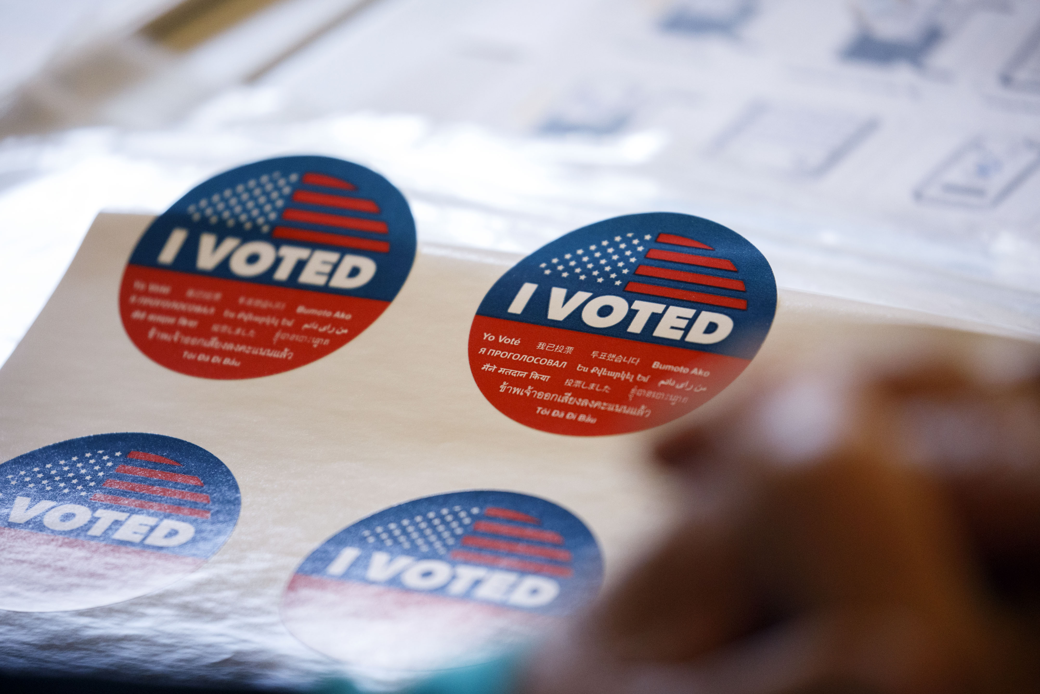 """Close up shot of red, white, and blue stickers that read """"I VOTED."""""""