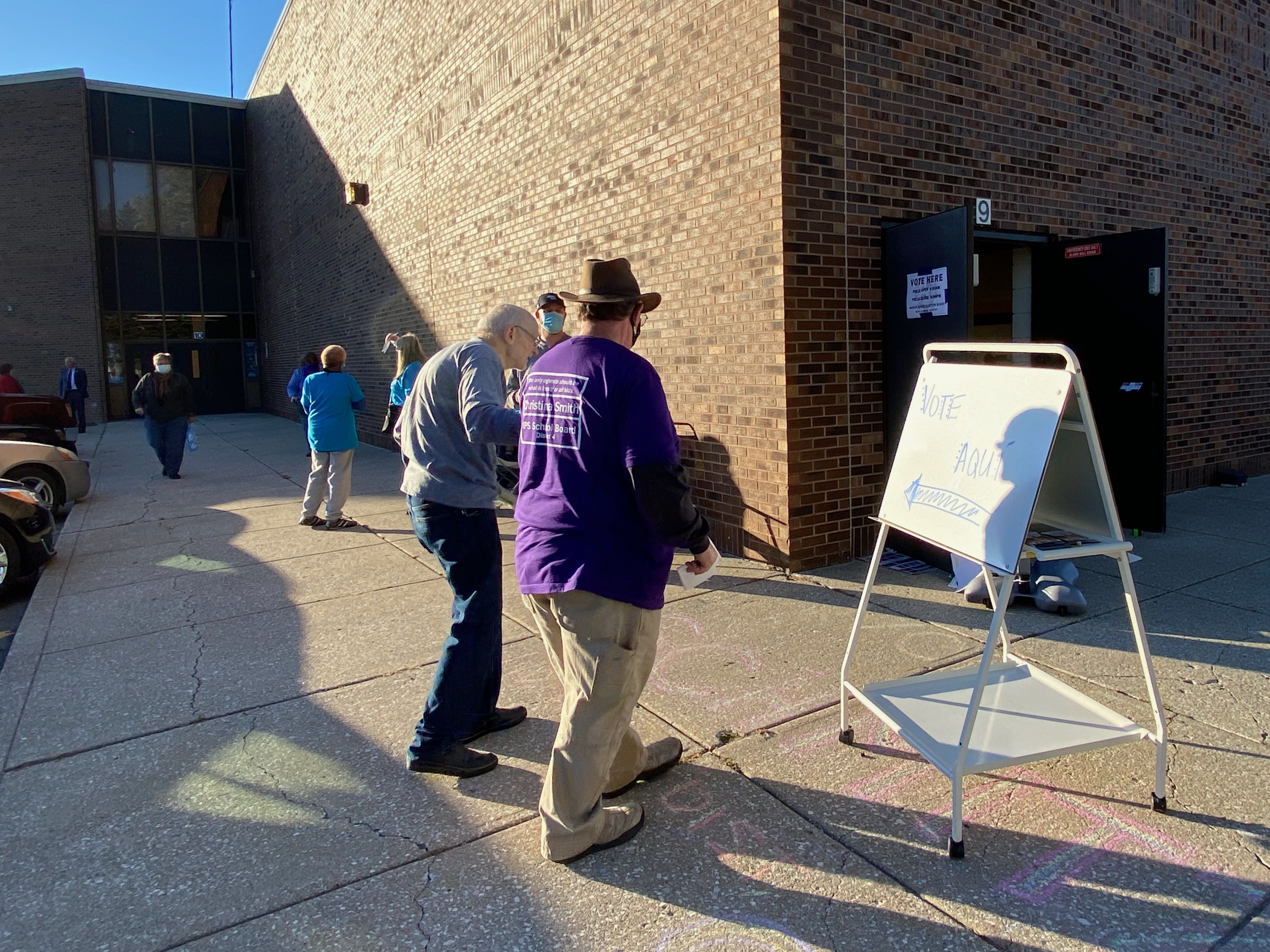 A campaign worker helps a man in to the polls.