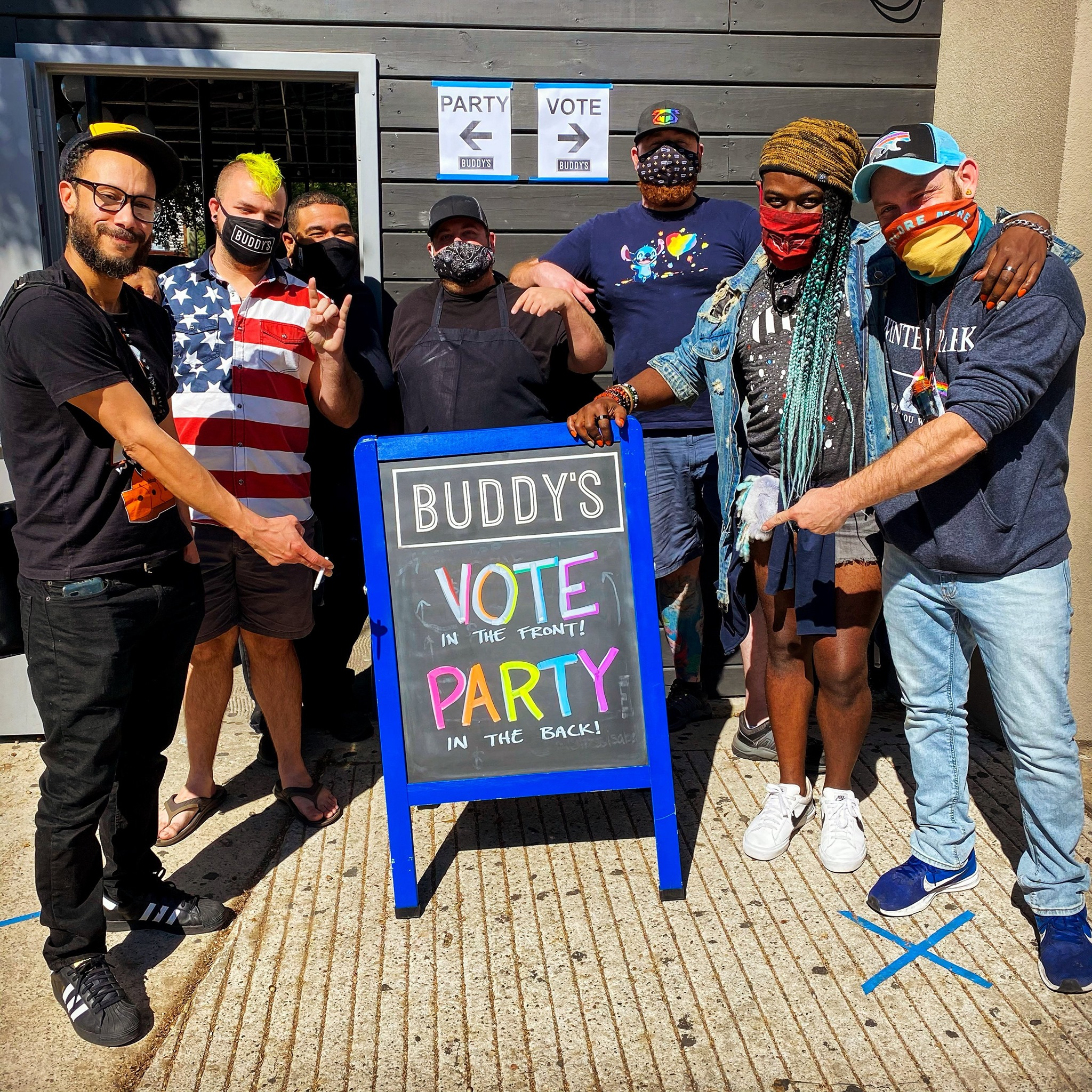 """a group of masked people stand in front of a sign that reads """"vote in the front, party in the back"""" outside a gay bar."""