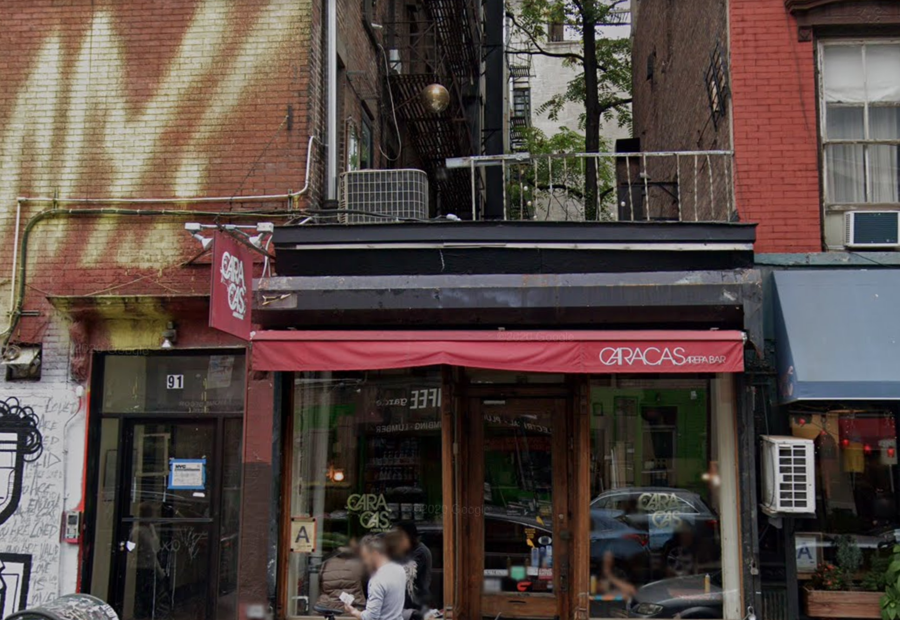 the exterior of a restaurant with a red awning that reads caracas arepa bar