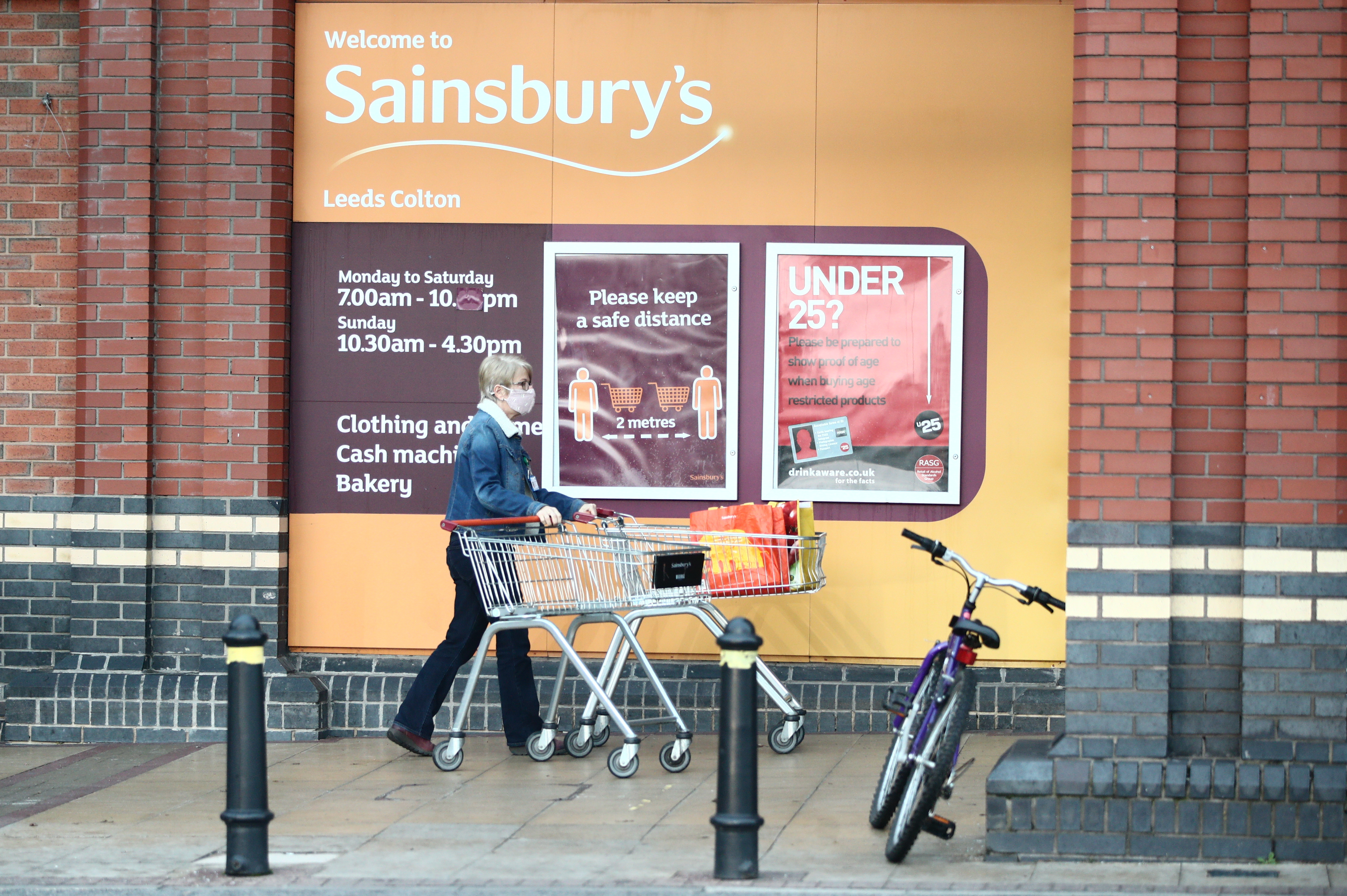 A customer in a mask stands outside a Sainsbury's supermarket with a trolley