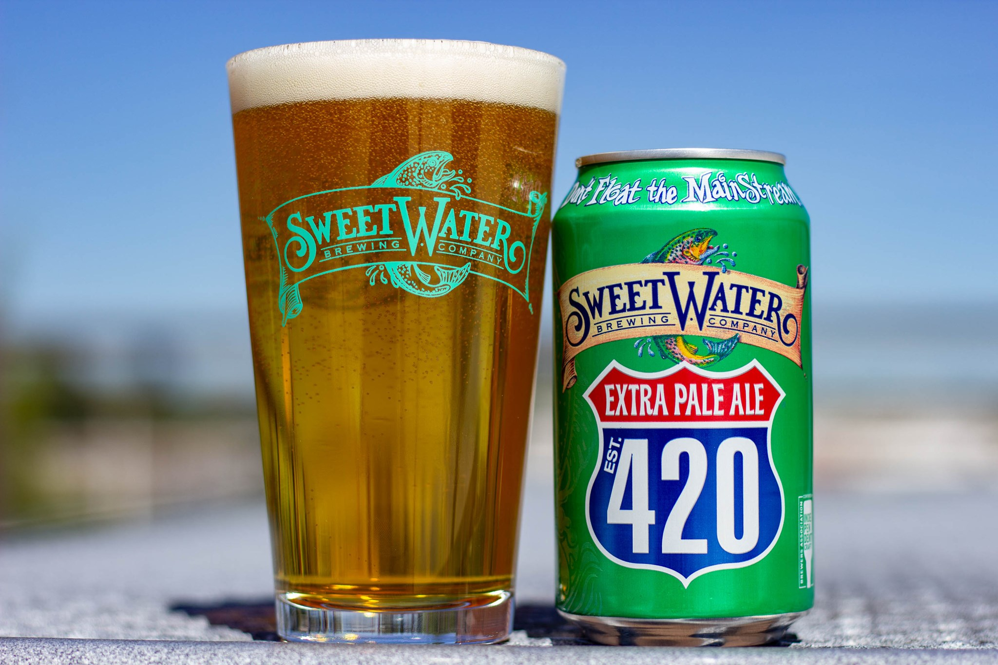 A pint of SweetWater Brewing Company's 420 Extra Pale Ale beside a green can with Extra Pale Ale 420 within a red and blue interstate highway logo