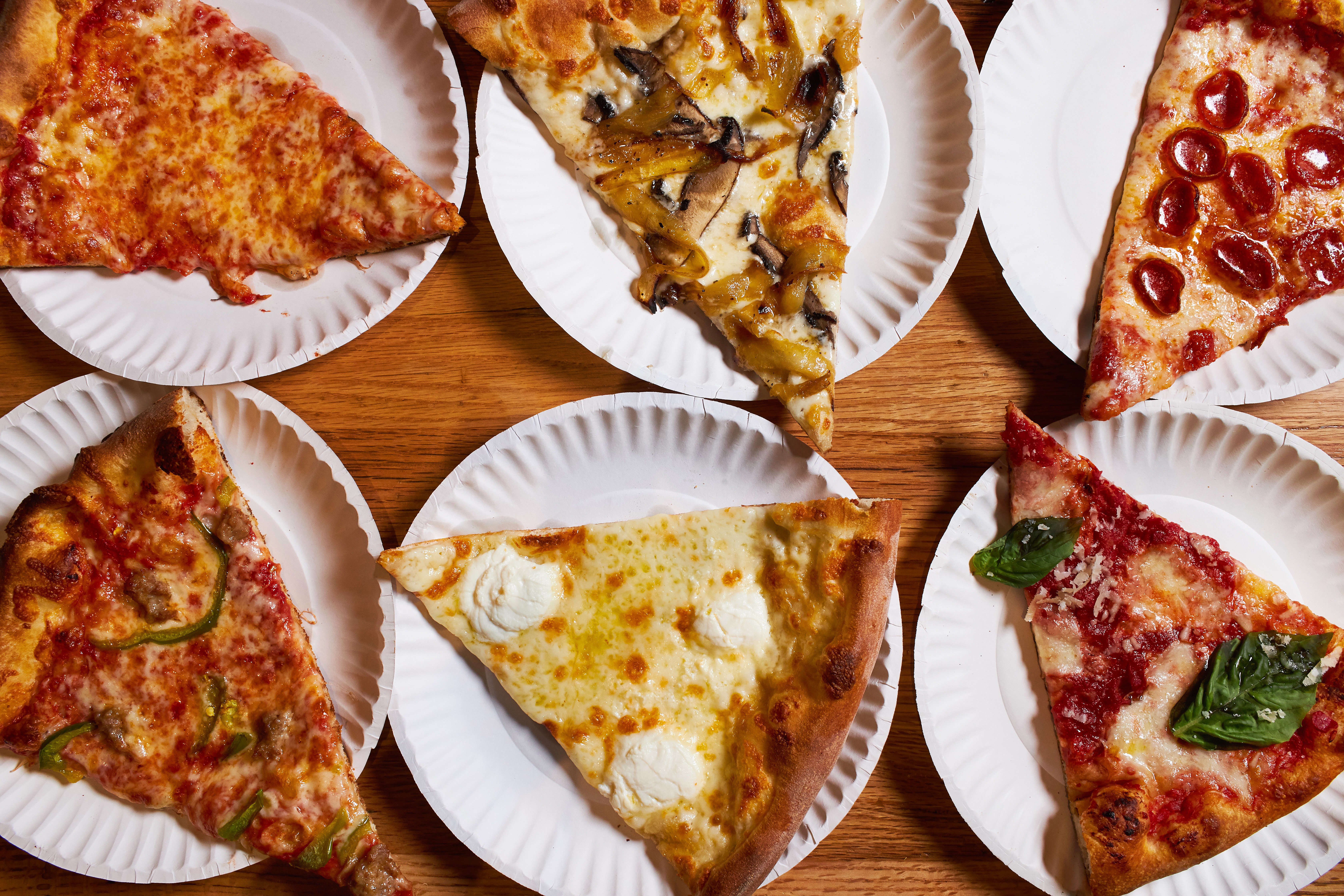 Several slices on pizza on paper plates on a table.