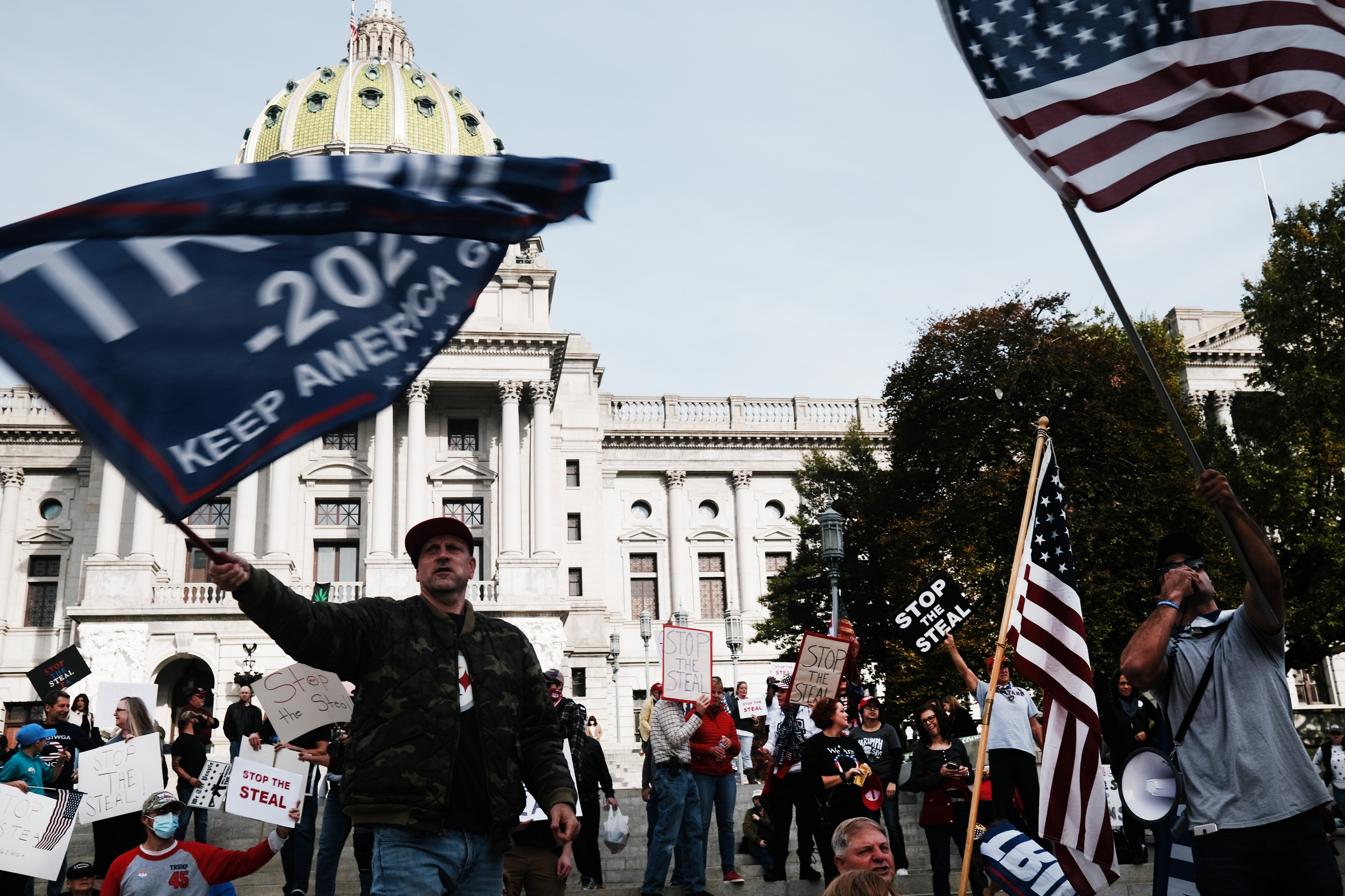 A protester waves a Trump flag in front of the Pennsylvania State Capitol building.