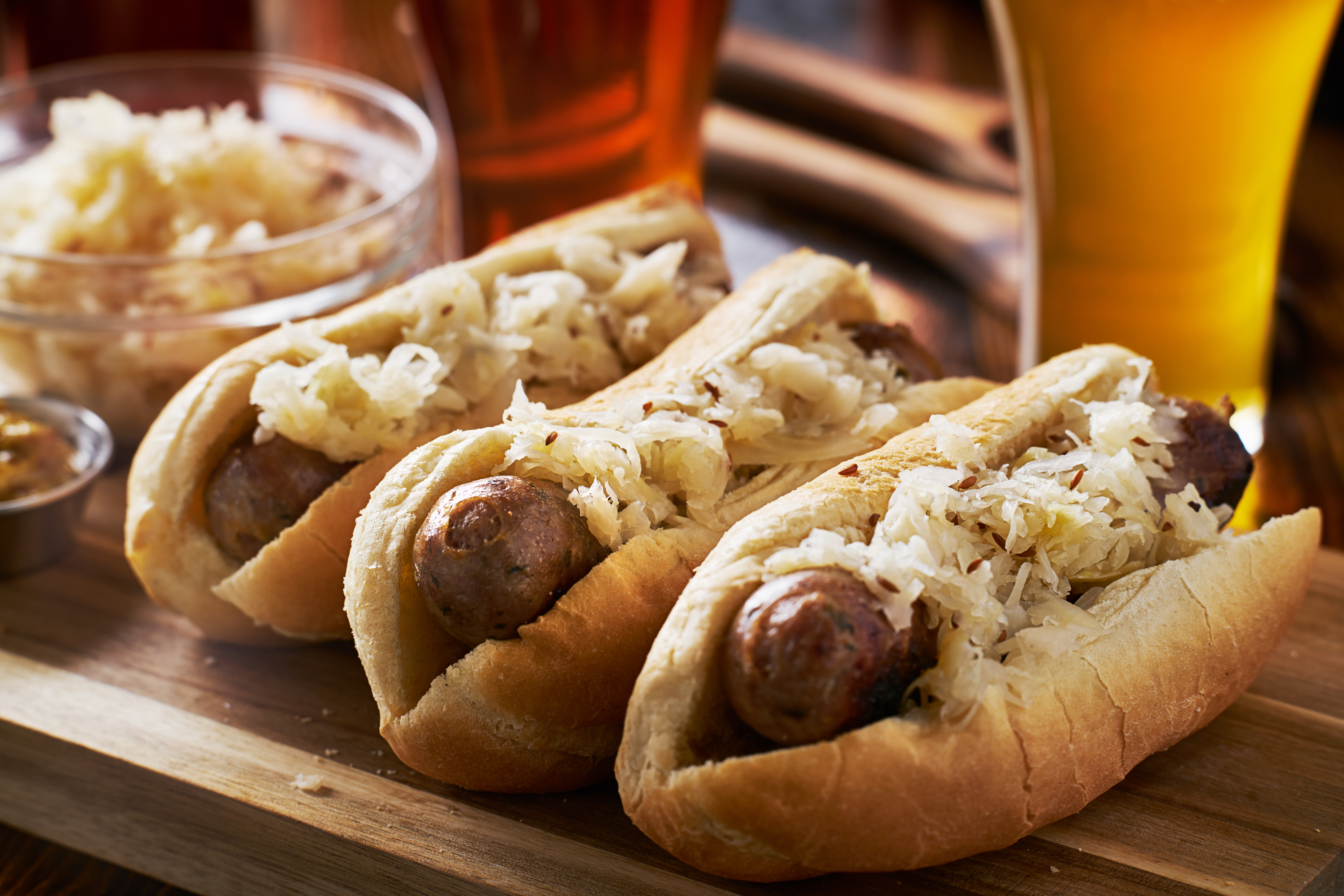 Three bratwursts in buns with toppings on a wooden table with beer in the background