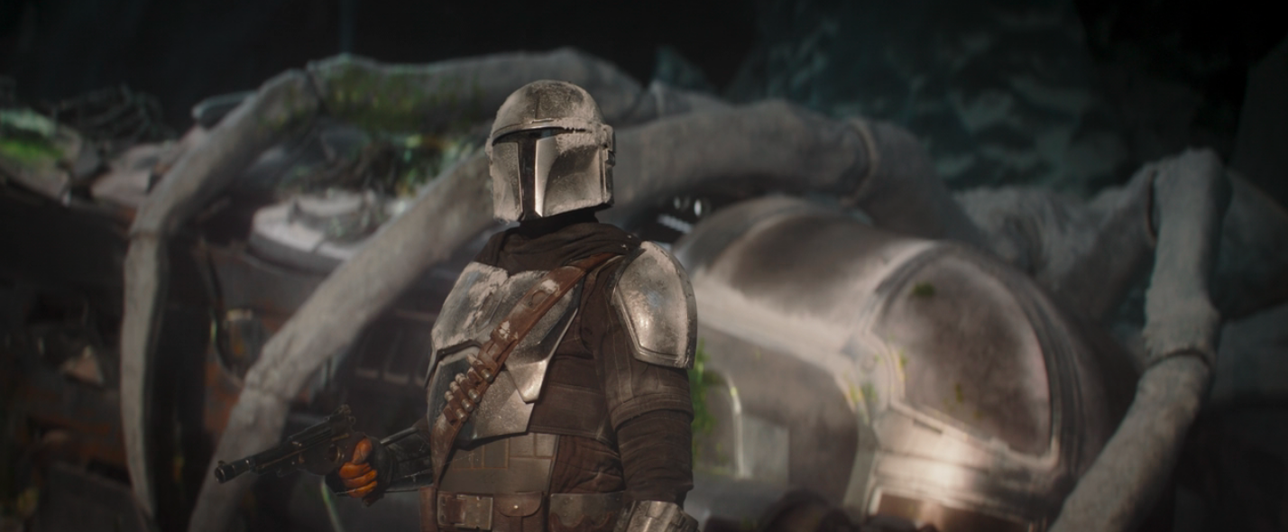 The Mandalorian stands with his pistol outside the Razor Crest on the ice spider planet