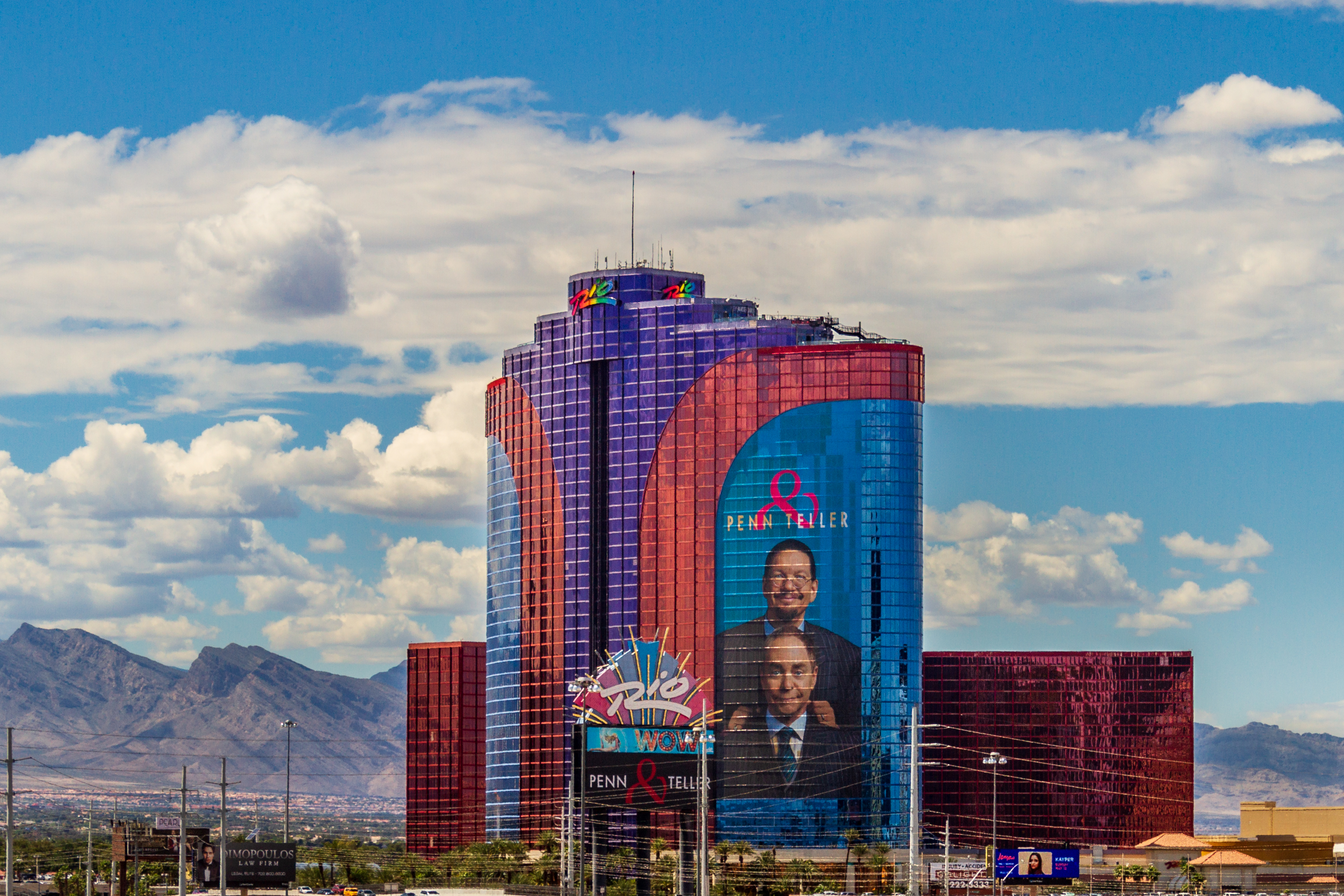 A hotel with blue, red, and purple windows with mountains and a blue cloudy sky behind it.