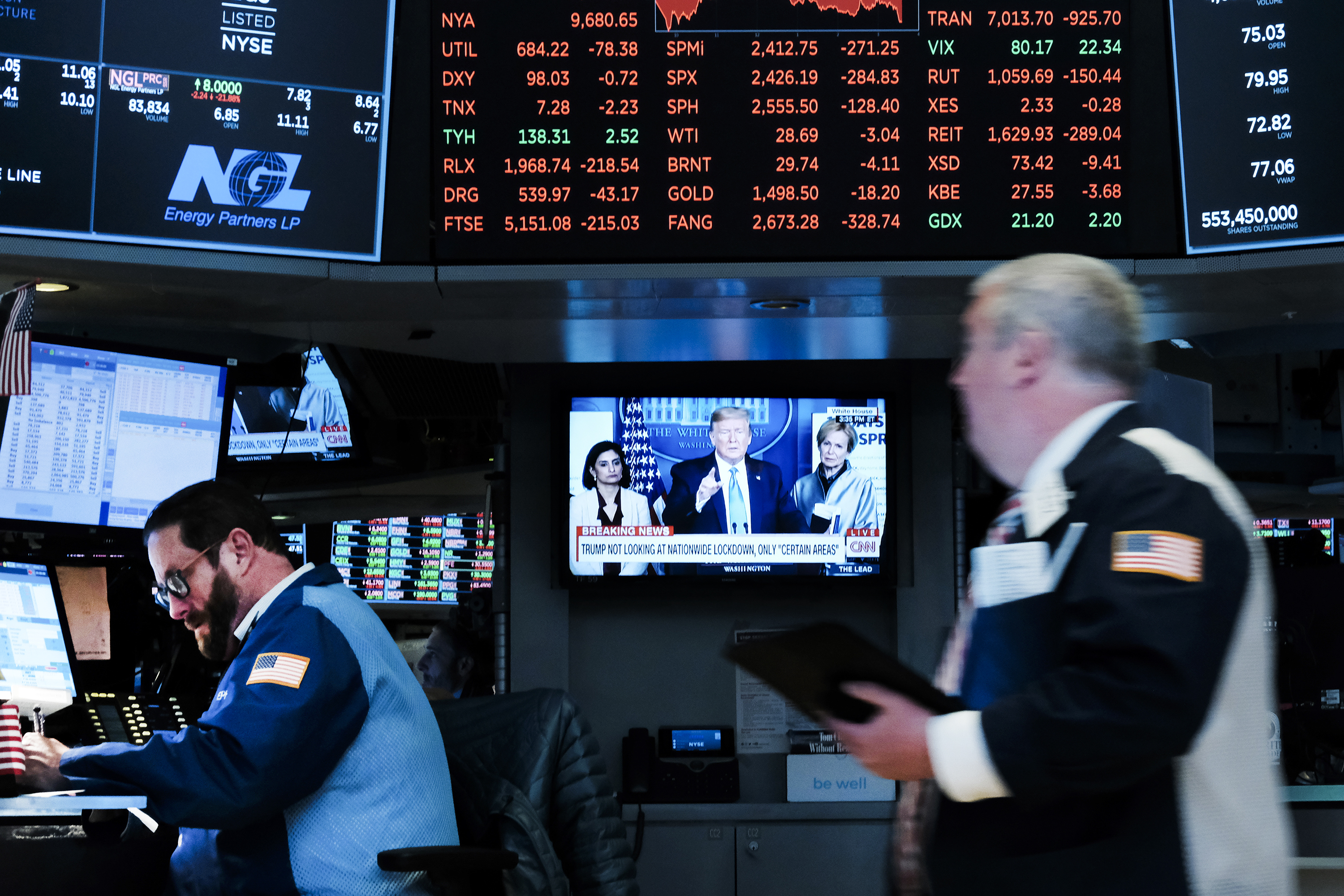 Two people on the floor of the New York Stock Exchange with a television screen showing a Trump news conference in the background.