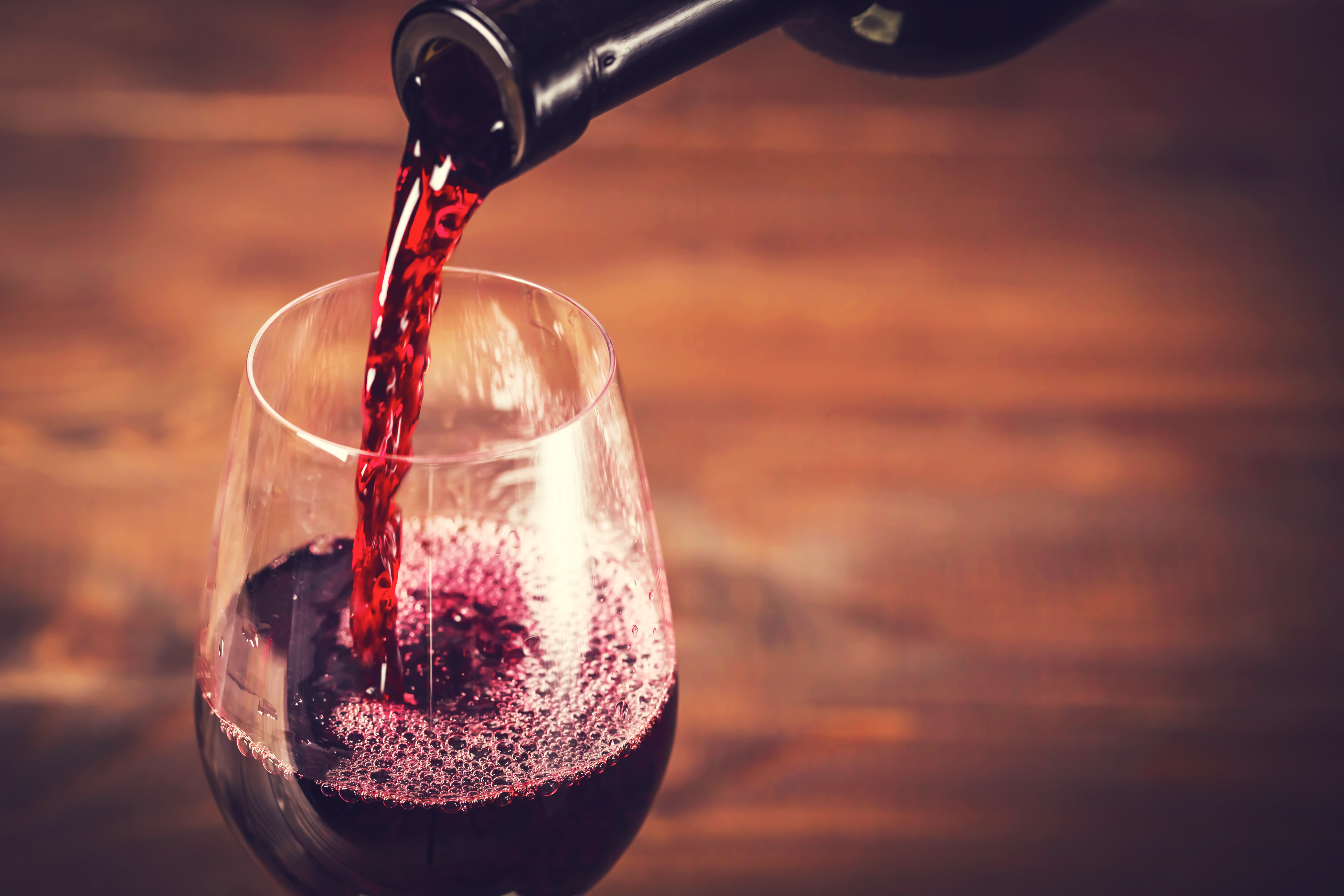 Bottle of red wine being poured into a glass