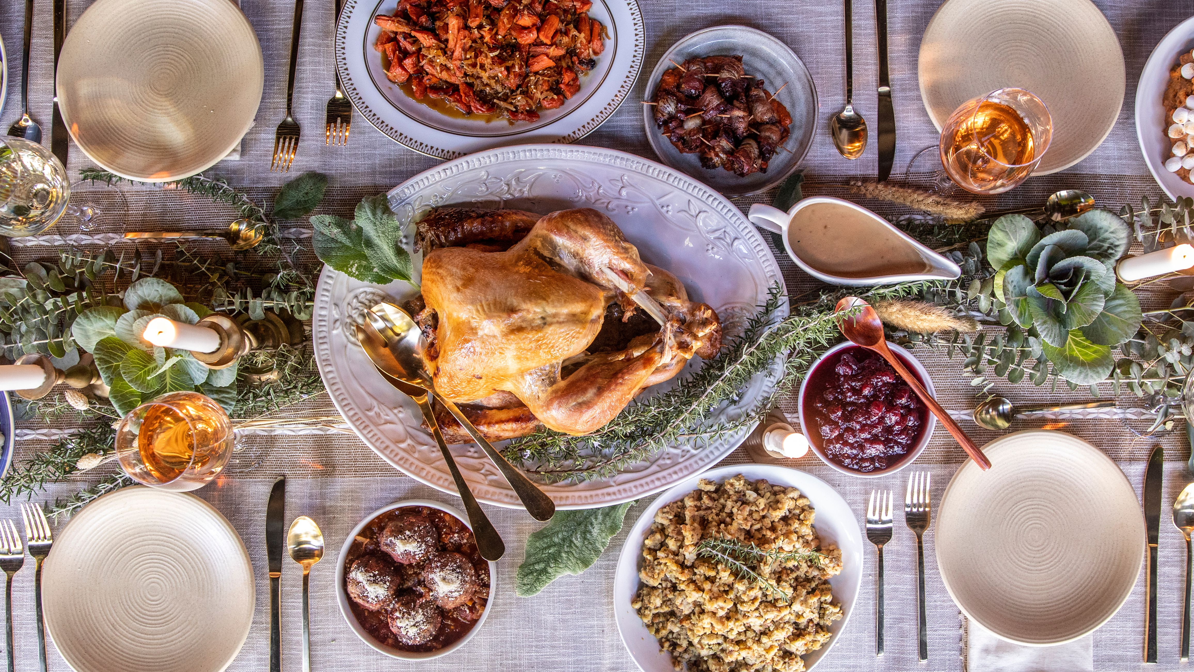 An overhead shot of a turkey dinner feast with all the Thanksgiving side dishes and trimmings