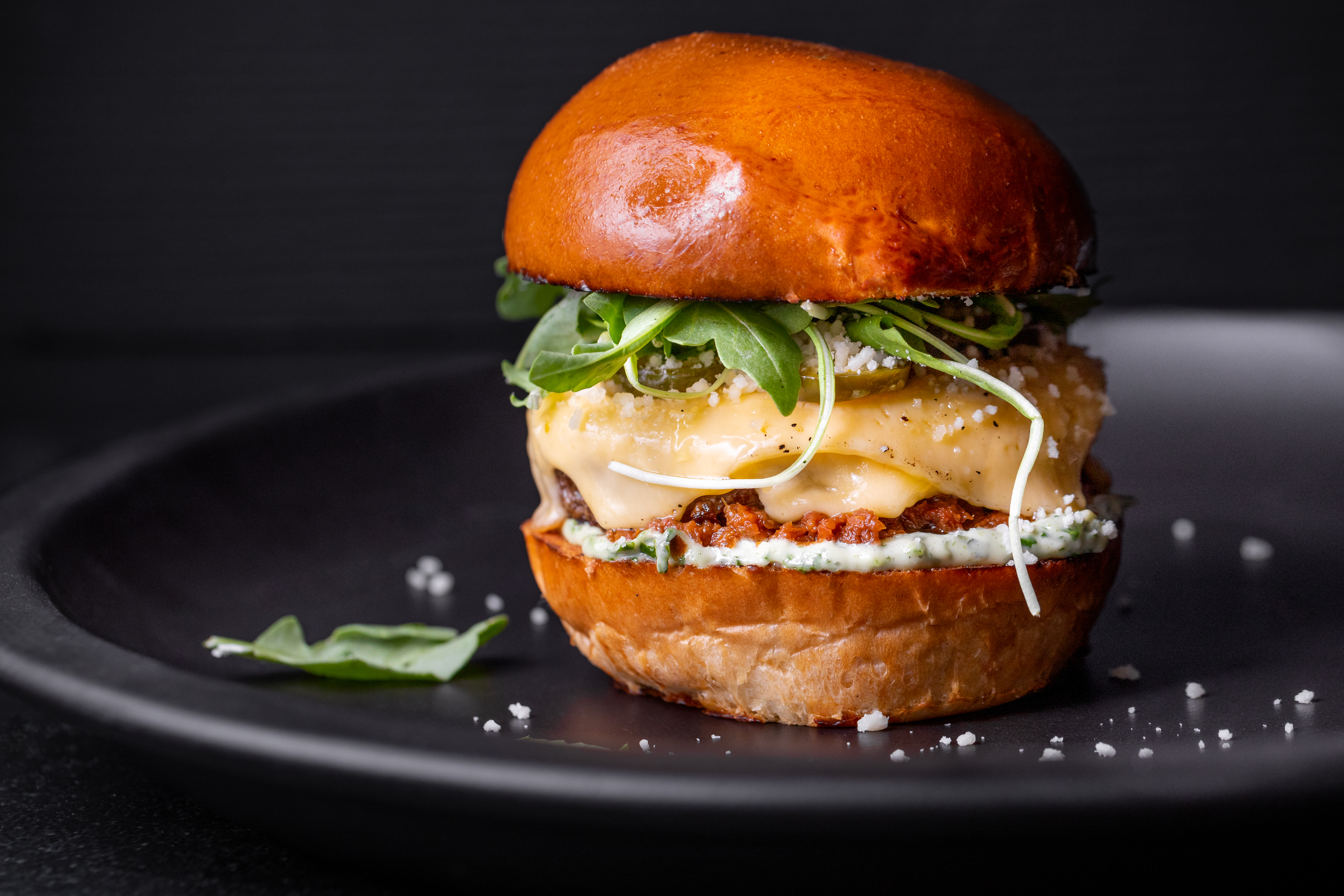 A tall burger on a golden brioche bun with lots of cheese and arugula.