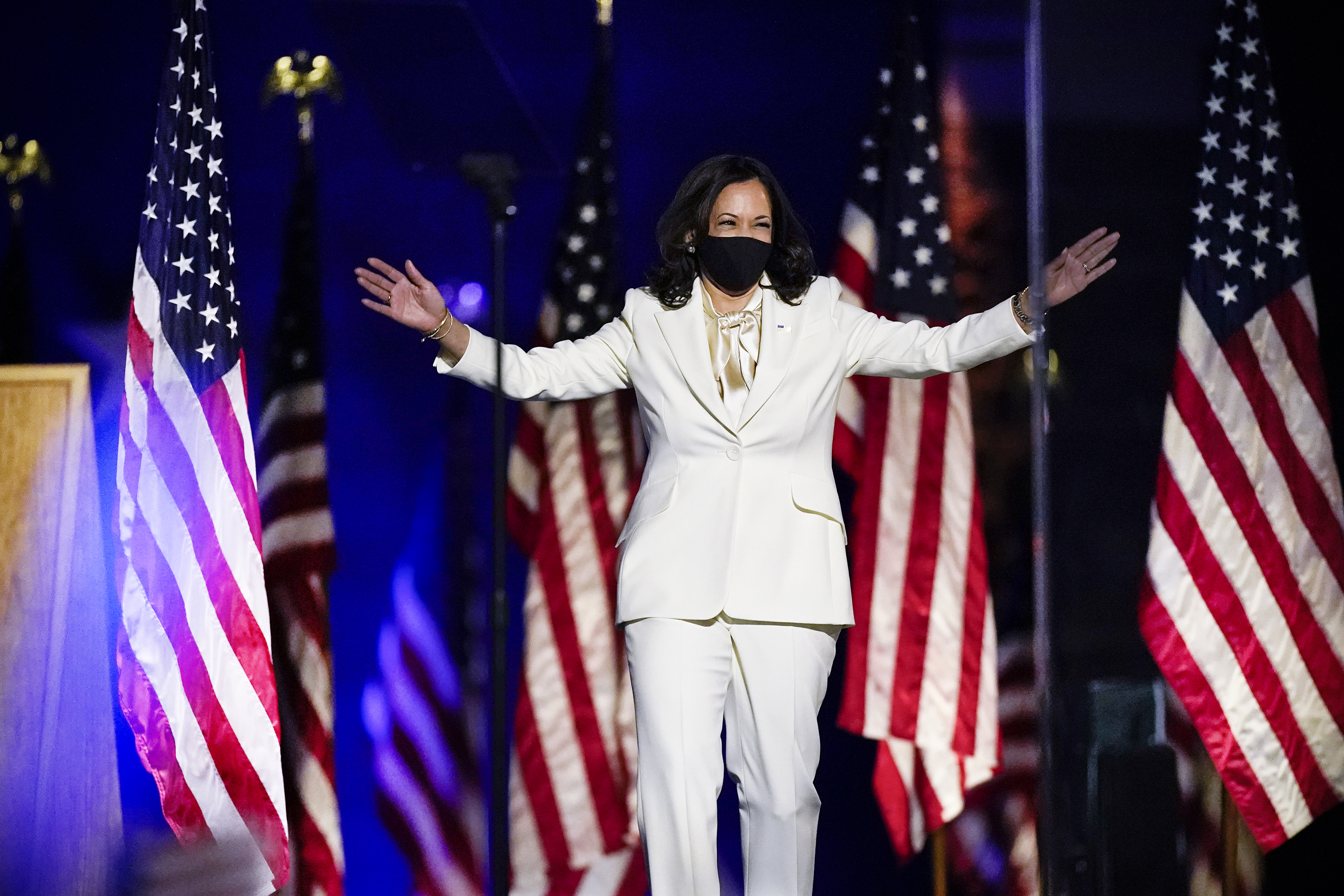 Harris spreads her arms as if hugging the crowd before her in a well-tailored white suit, white silk pussy-bow blouse, and black face mask. Behind her is a row of US flags, and she is illuminated by blue spotlights.